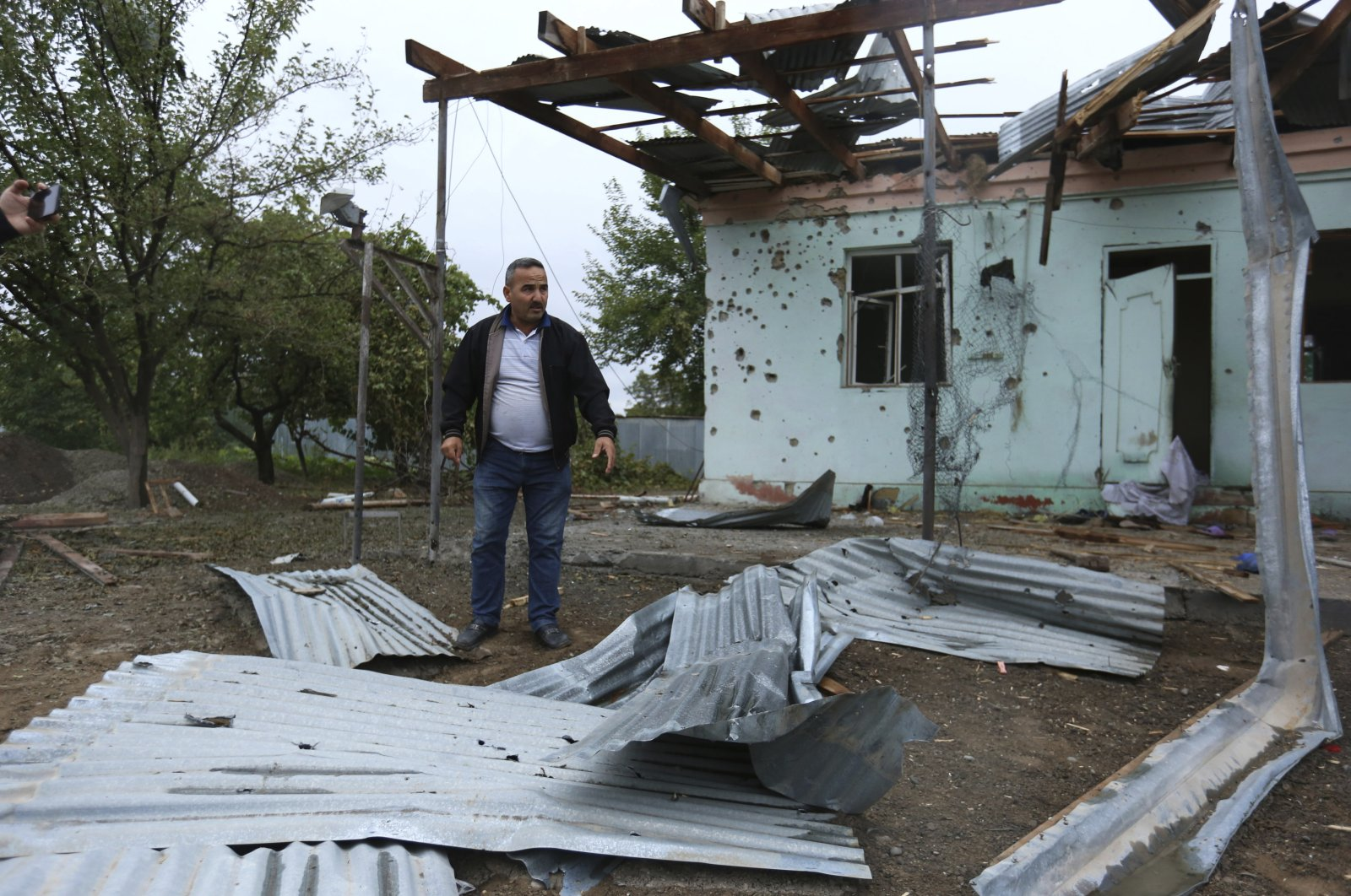 A man stands in a yard of a destroyed house damaged by shelling during fighting over the region of Nagorno-Karabakh in Agdam, Azerbaijan, Oct. 1, 2020. (AP Photo)