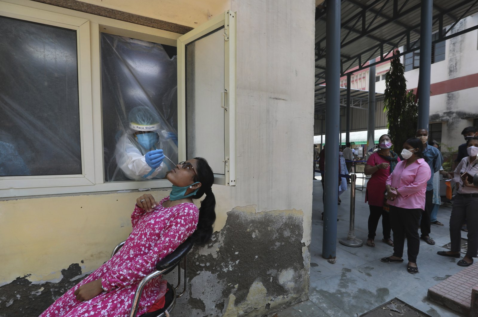 A health worker takes a nasal swab sample to test for COVID-19, as others await their turn in New Delhi, India, Saturday, Sept. 5, 2020. (AP Photo)