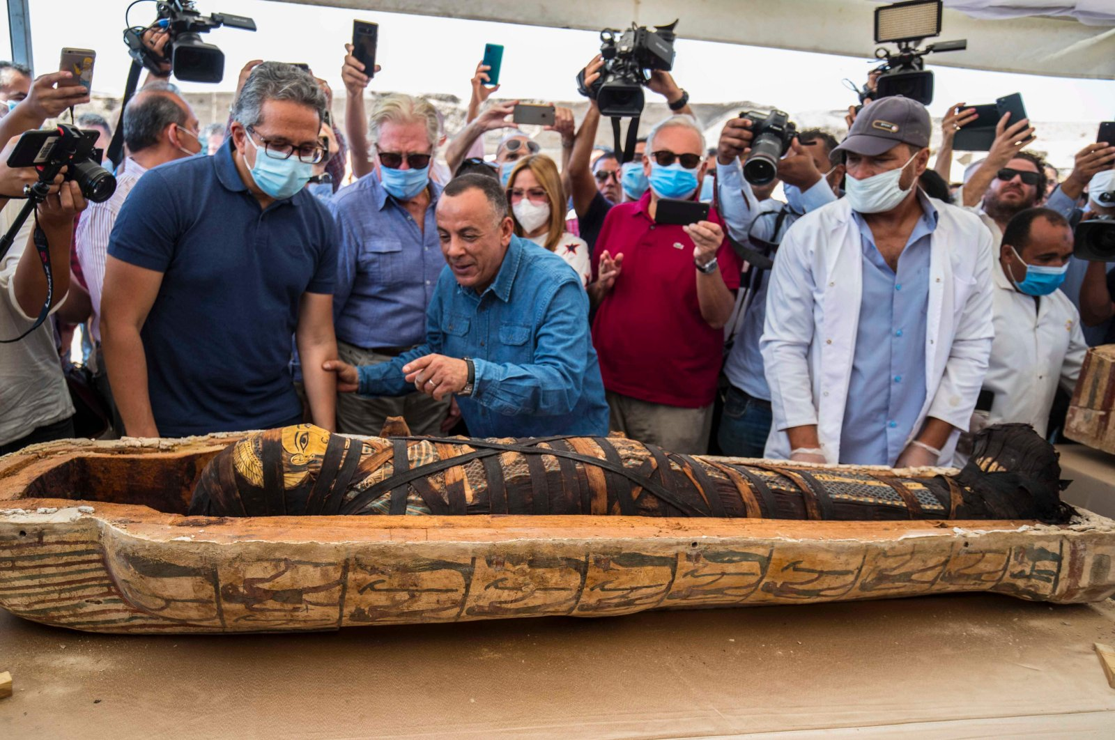 A picture taken on October 3, 2020 shows Egyptian Minister of Tourism and Antiquities Khaled Al-Anani (L), and Mustafa Waziri (R), Secretary General of the Supreme Council of Antiquities, unveil the mummy inside a sarcophagus excavated by the Egyptian archaeological mission working at the Saqqara necropolis, (AFP Photo)