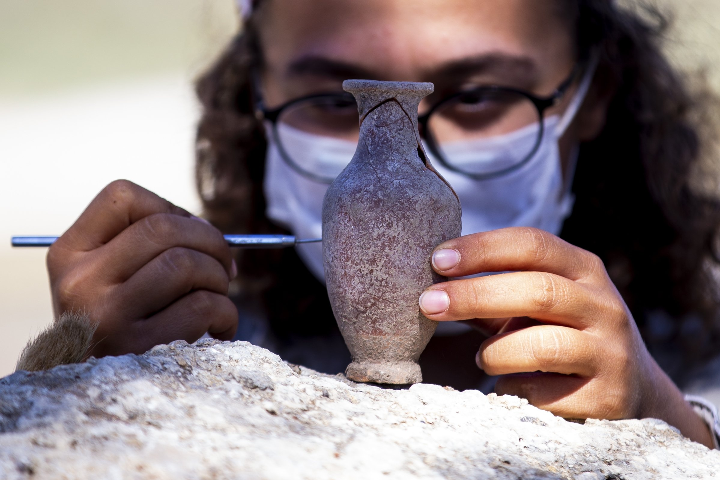 An archaeologist works on a fragrance container found in the ancient city of Patara, Antalya, southern Turkey, Oct. 3, 2020. (AA PHOTO)
