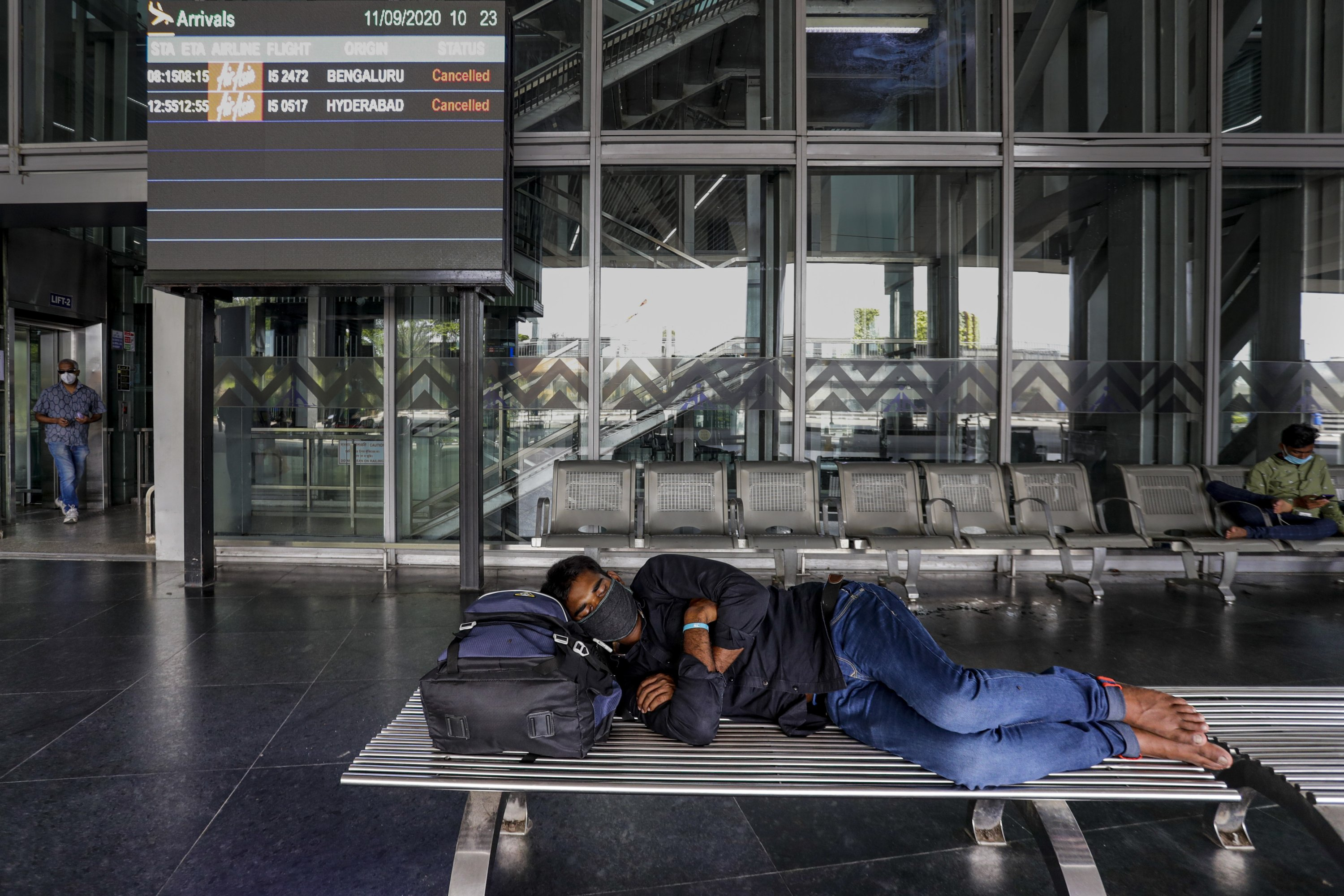 A stranded passenger sleeps outside an airport as an electronic board flashes cancellation of flights, during a complete lockdown in Kolkata, India, Sept. 11, 2020. (AP Photo)