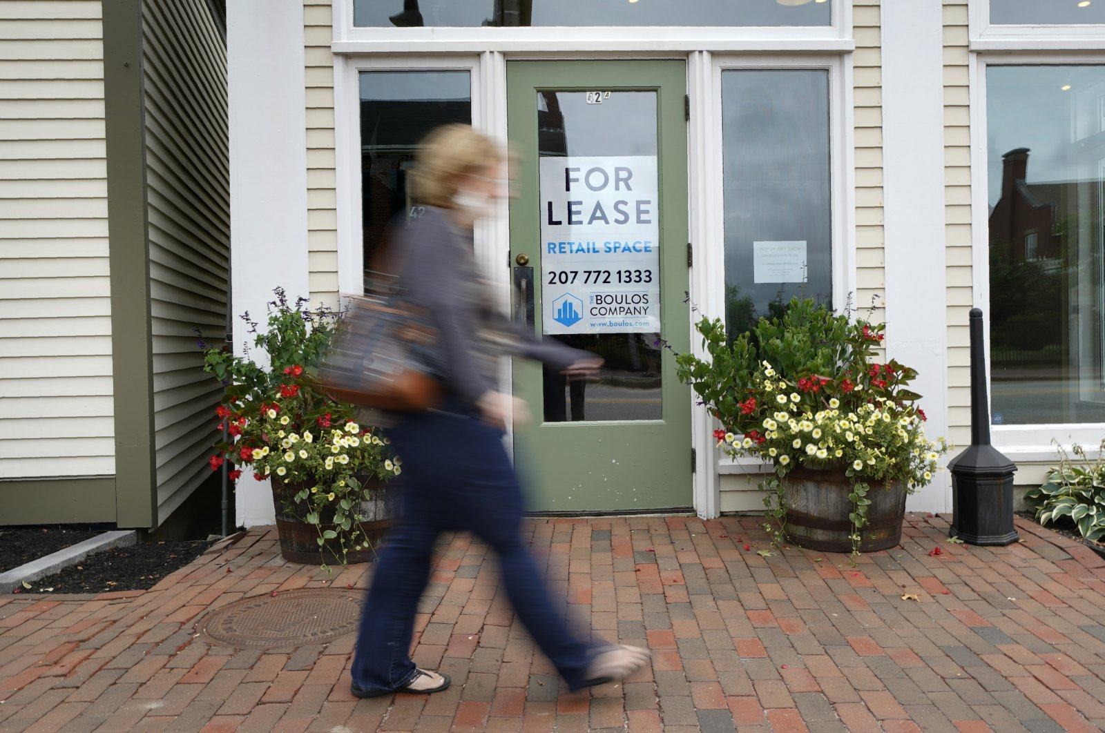 A shopper walks by one of several vacant retail spaces among the outlet shops in Freeport, Maine, U.S., Sept. 2, 2020. (AP Photo)