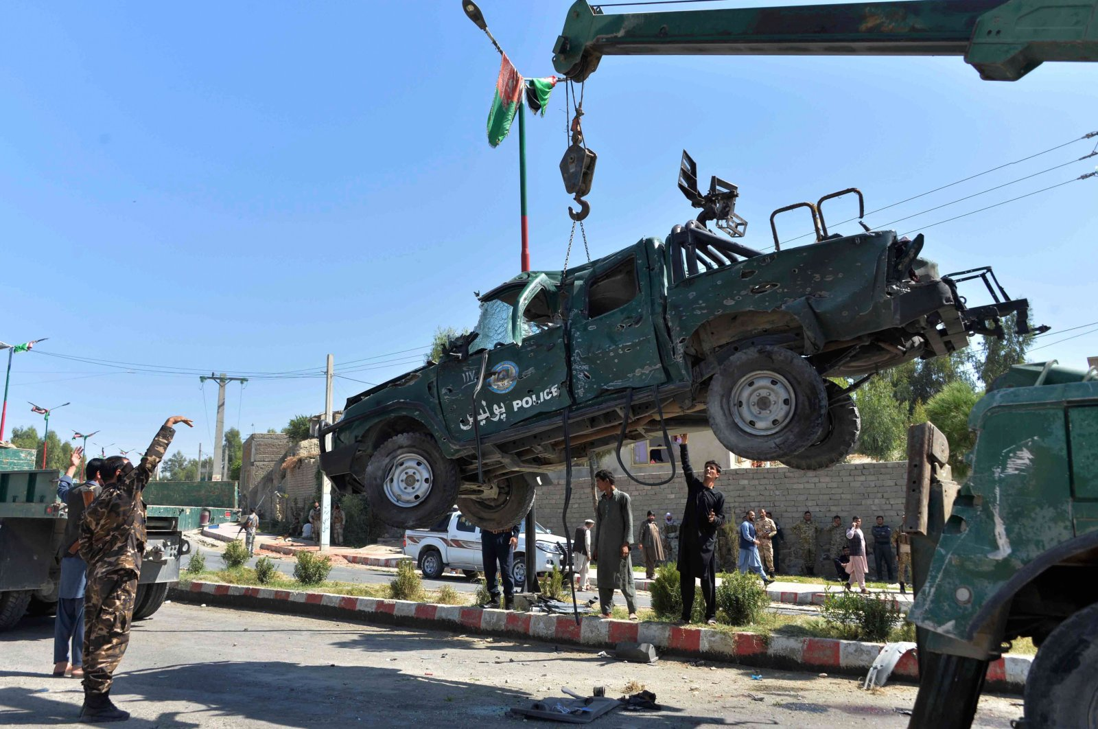 Afghan security forces remove a damaged police vehicle at the site of a car bomb attack that targeted Laghman provincial governor's convoy, in Mihtarlam, Laghman Province on Oct. 5, 2020. (AFP Photo)
