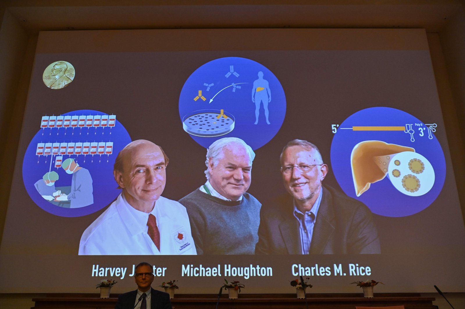 Nobel Committee member Patrik Ernfors sits in front of a screen displaying the winners of the 2020 Nobel Prize in Physiology or Medicine, (L-R) American Harvey Alter, Briton Michael Houghton and American Charles Rice, during a press conference at the Karolinska Institute in Stockholm, Sweden, on October 5, 2020. (AFP Photo)