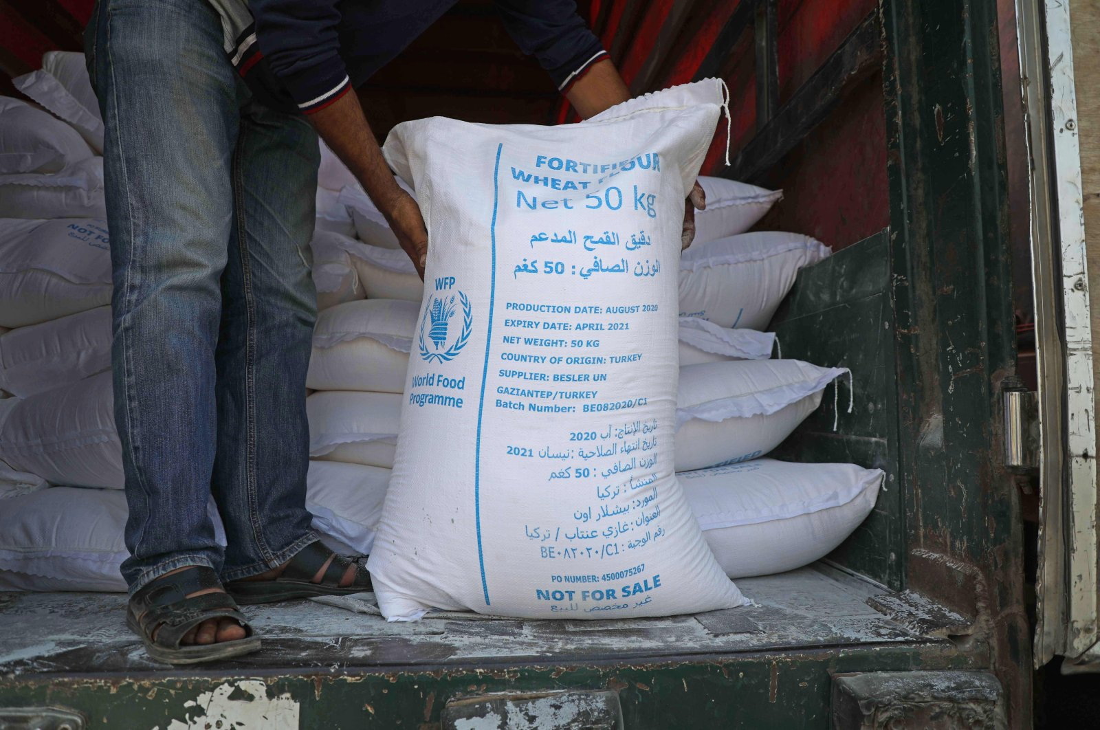 A man unloads bags of fortified flour from an international humanitarian aid truck that crossed into Syria's northwestern Idlib province through the Bab al-Hawa border crossing with Turkey, Sept. 7, 2020. (AFP Photo)