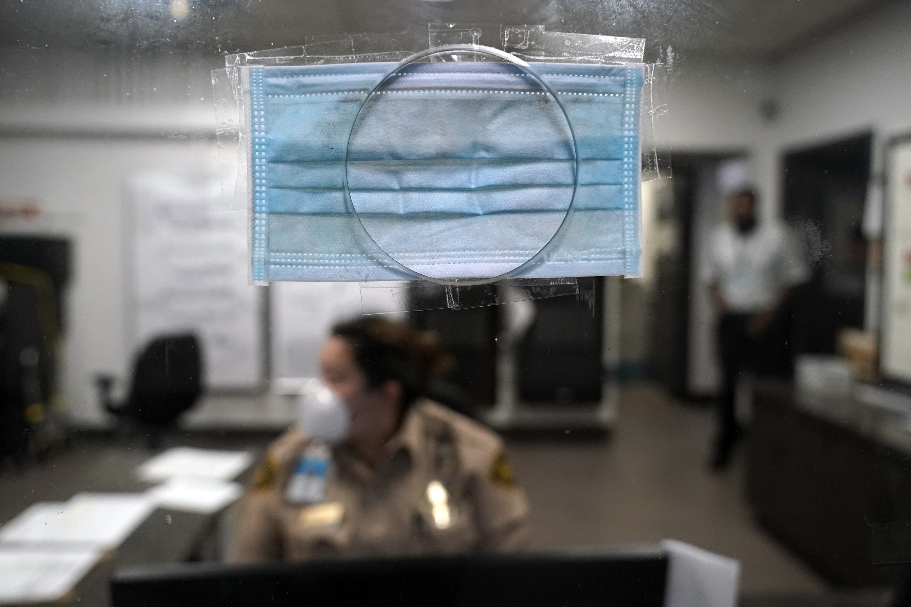 A mask covers a security office checkin window opening at a homeless shelter inside the San Diego Convention Center, Aug. 11, 2020, in San Diego. (AP Photo)