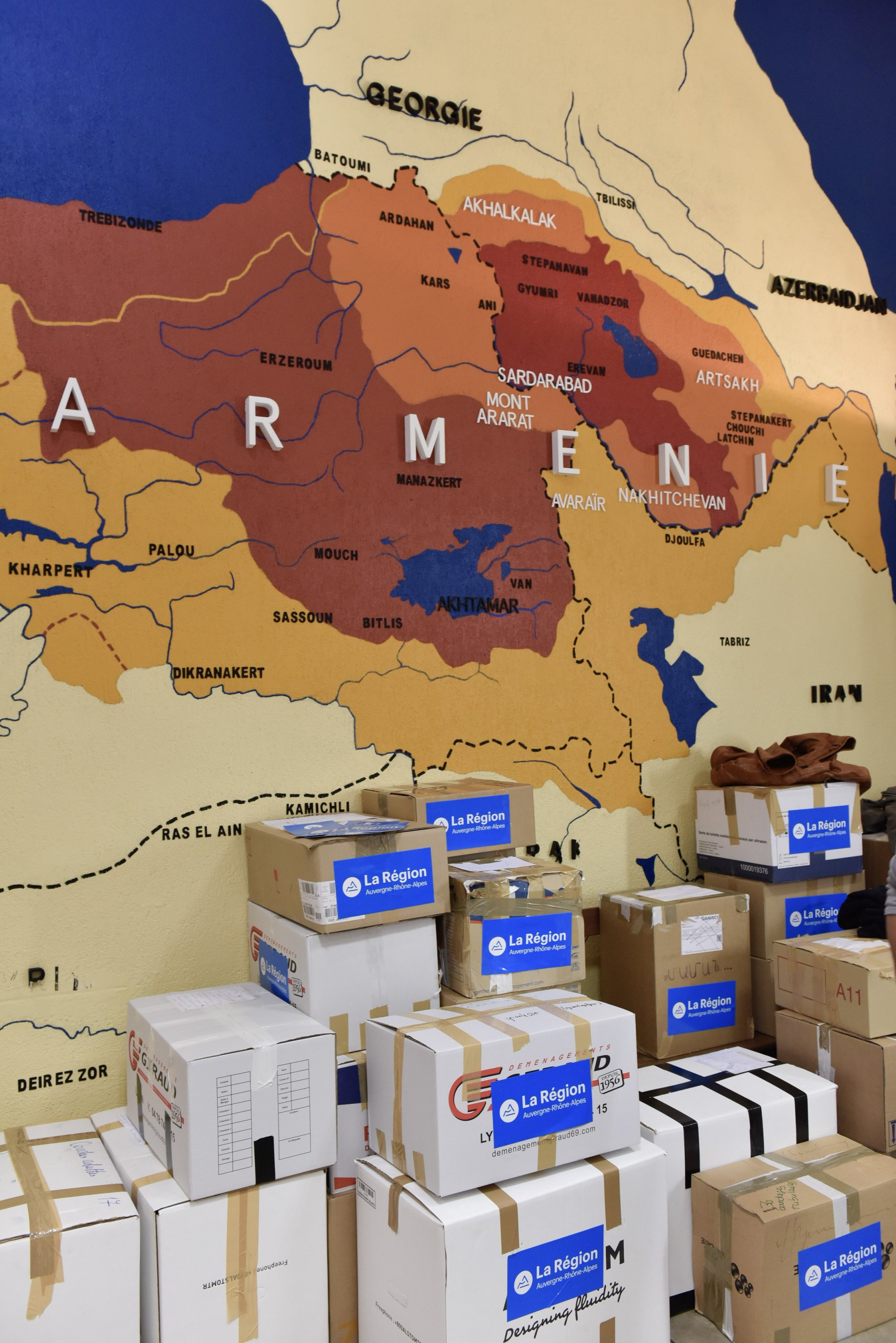 A map showing parts of eastern Turkey within the borders of Armenia is seen on a wall behind boxes of medical supplies at an event in the Auvergne-Rhone-Alpes region of France, in a photo shared Oct. 6, 2020. (Photo from Twitter @laurentwauquiez)