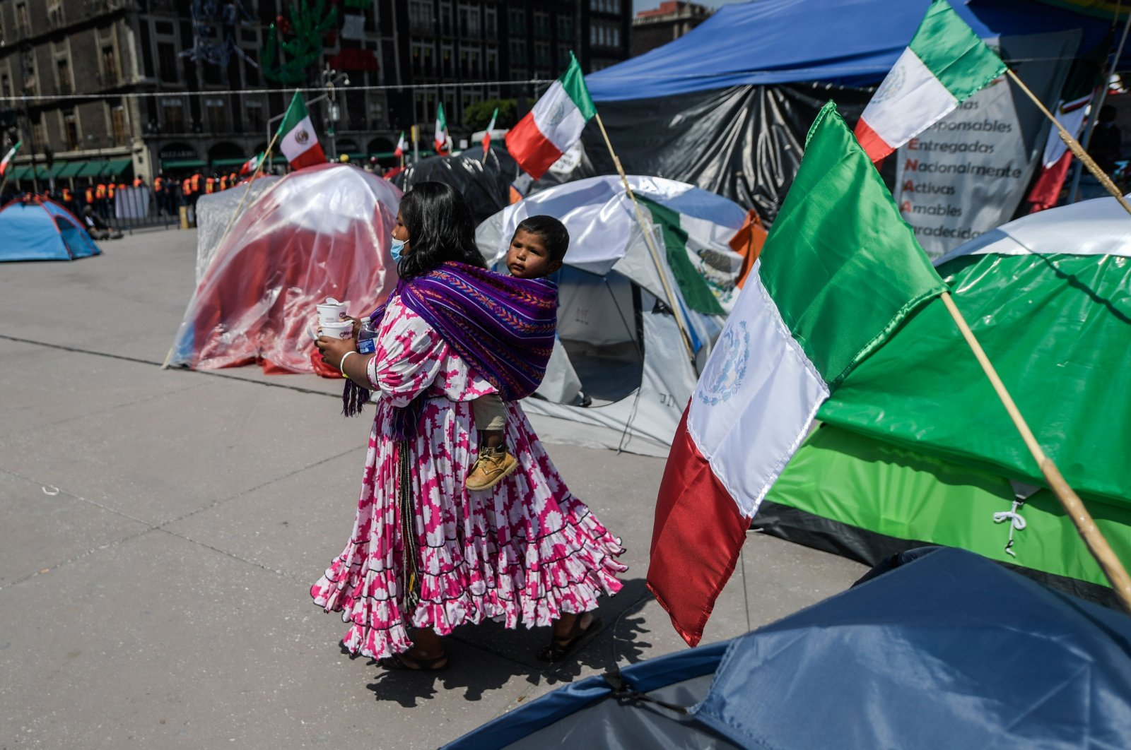 A woman of the Raramuri ethnic group walks amid tents set up by members of the National Front Anti-AMLO to protest against Mexican President Andres Manuel Lopez Obrador at Zocalo Square in Mexico City, on Oct. 5, 2020. (AFP Photo)