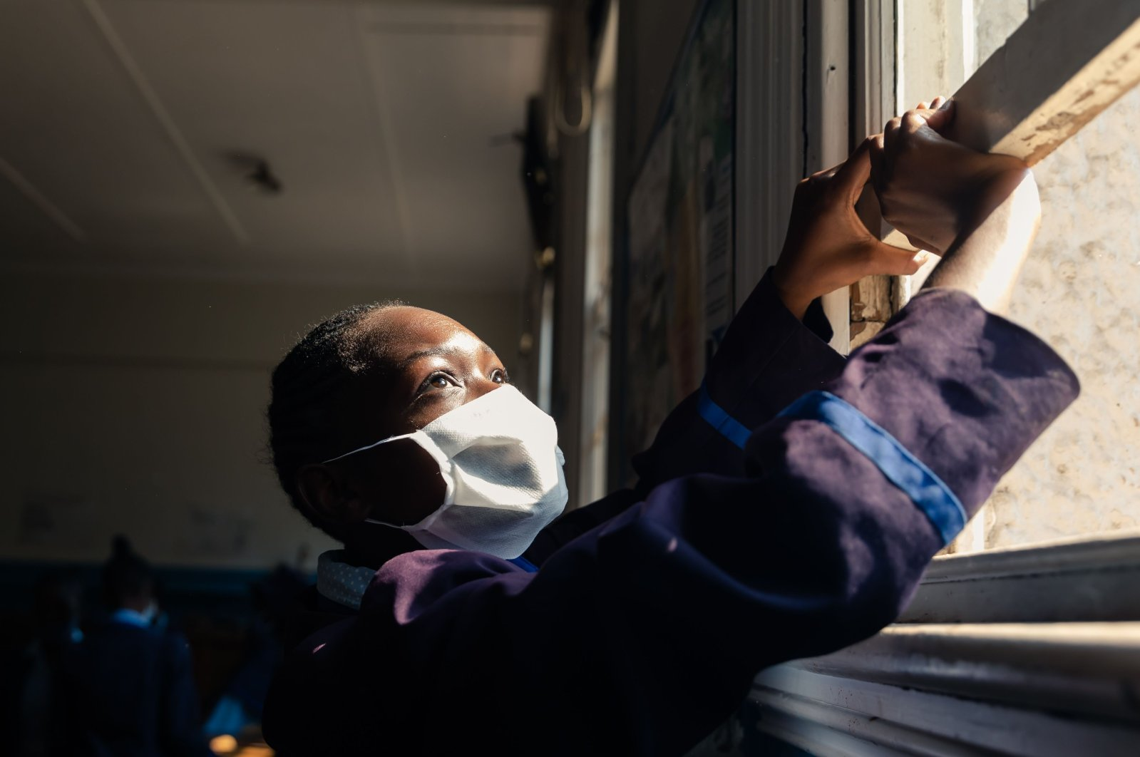 A pupil opens a window for fresh air circulation in the class room ahead of the first day of the resumption of classes at Queen Elizabeth School in Harare on September 28, 2020. (AFP Photo)
