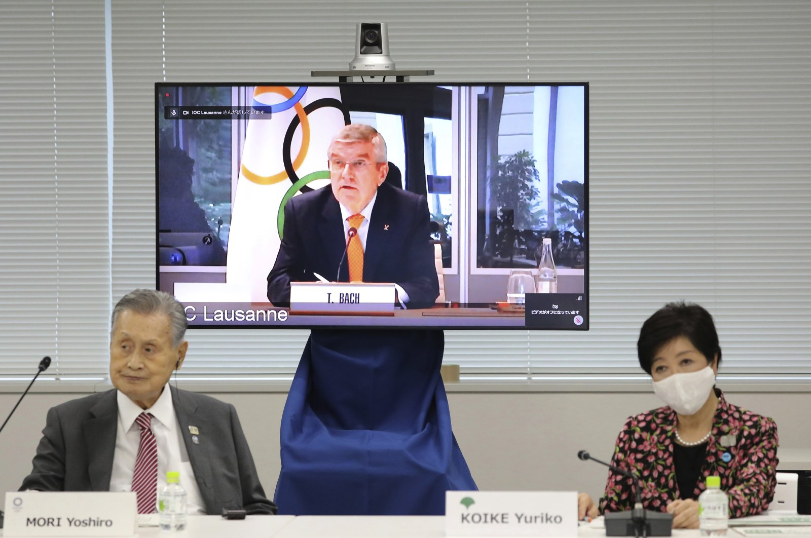IOC President Thomas Bach, on the screen, speaks remotely with Tokyo 2020 Organizing Committee President Yoshiro Mori (L) and Tokyo Gov. Yuriko Koike, during an online meeting, in Tokyo, Japan, Sept. 24, 2020. (AP Photo)