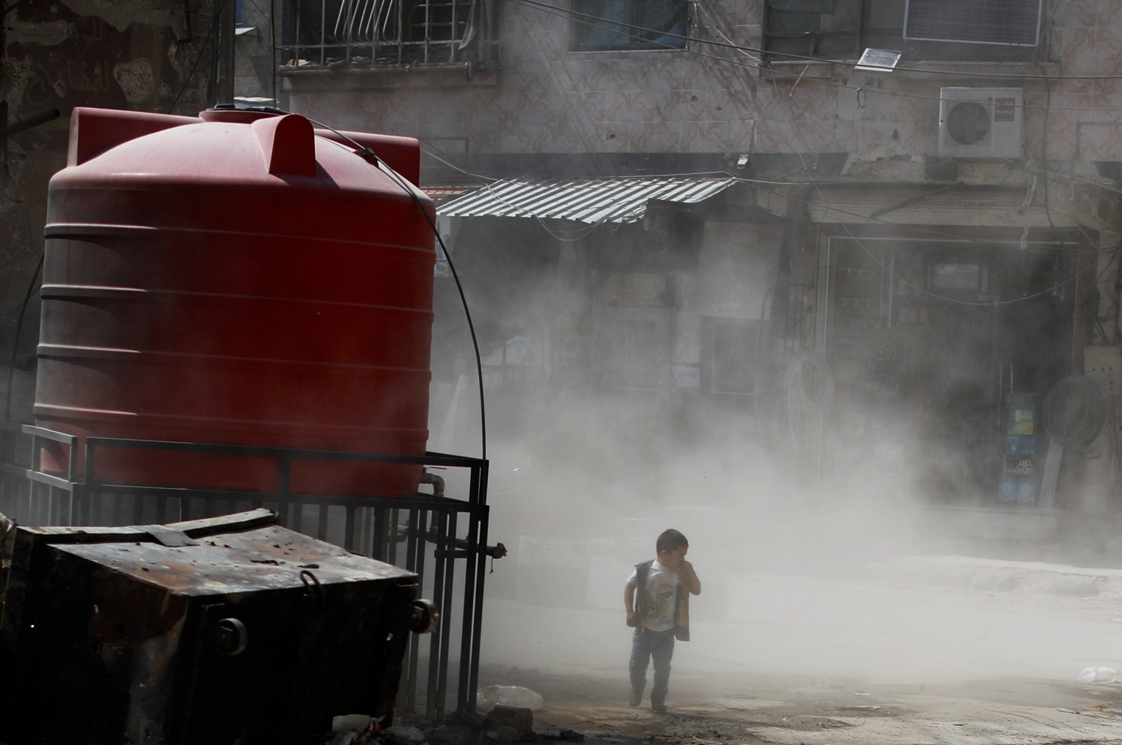 In this Sunday, July 15, 2018, photo, a Syrian boy walks amid a cloud of dust as a bulldozer remove debris from destroyed buildings, in the town of Douma in the eastern Ghouta region, near the Syrian capital Damascus. (AP File Photo)