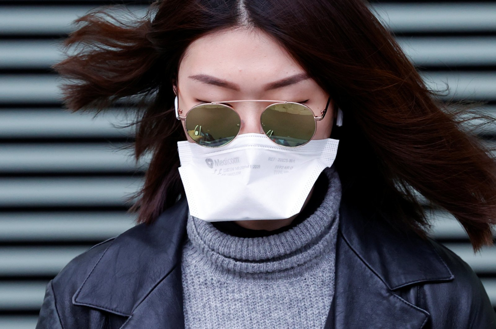 A woman wearing a face mask leaves XIII district police station in Paris, after a suspected coronavirus case was examined, France February 24, 2020. (Reuters Photo)
