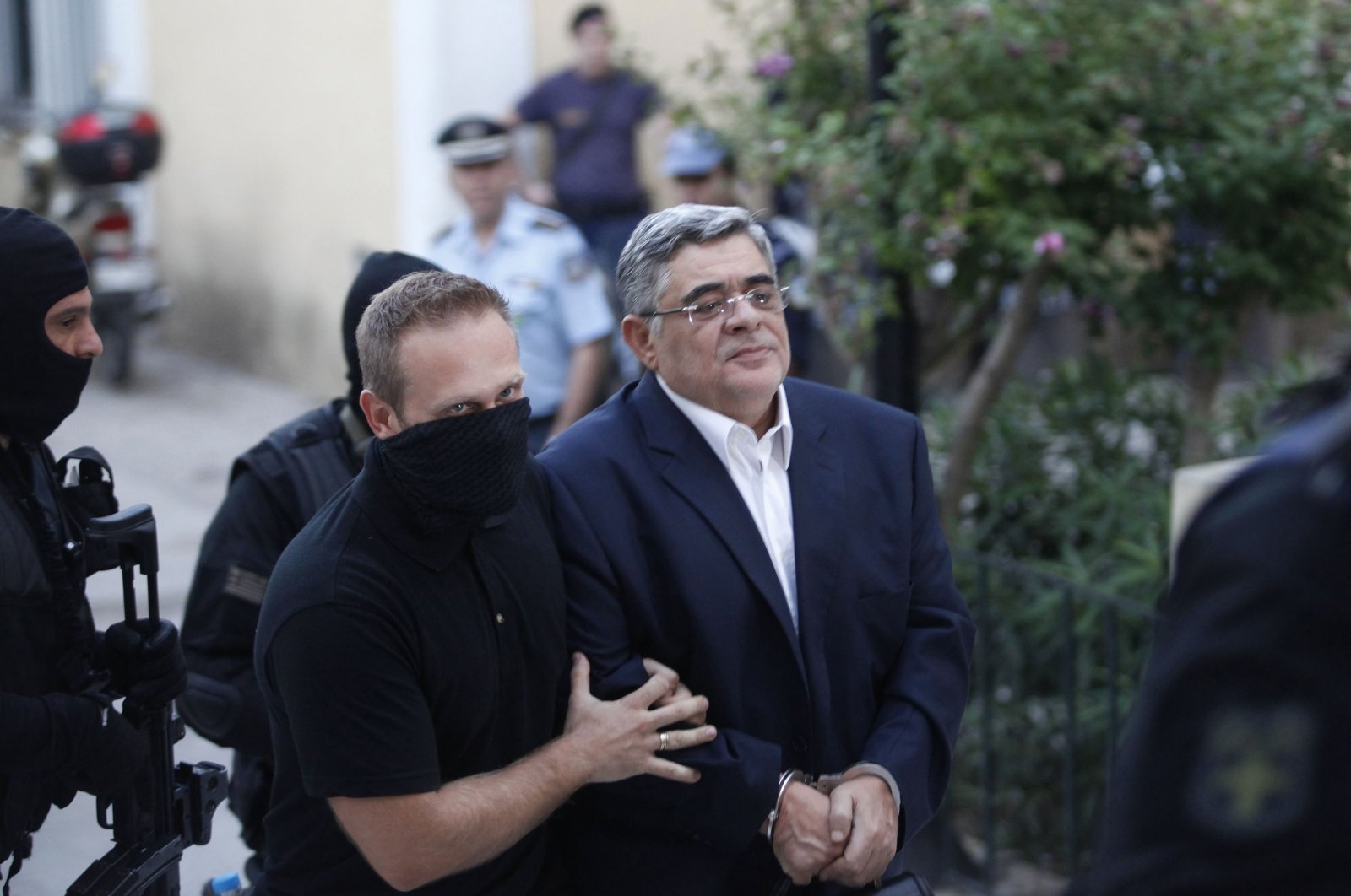 Far-right Golden Dawn party leader Nikos Mihaloliakos (R) is escorted by anti-terrorism police officers as he arrives at a courthouse in Athens, Greece, Sept. 28, 2013. (Reuters Photo)