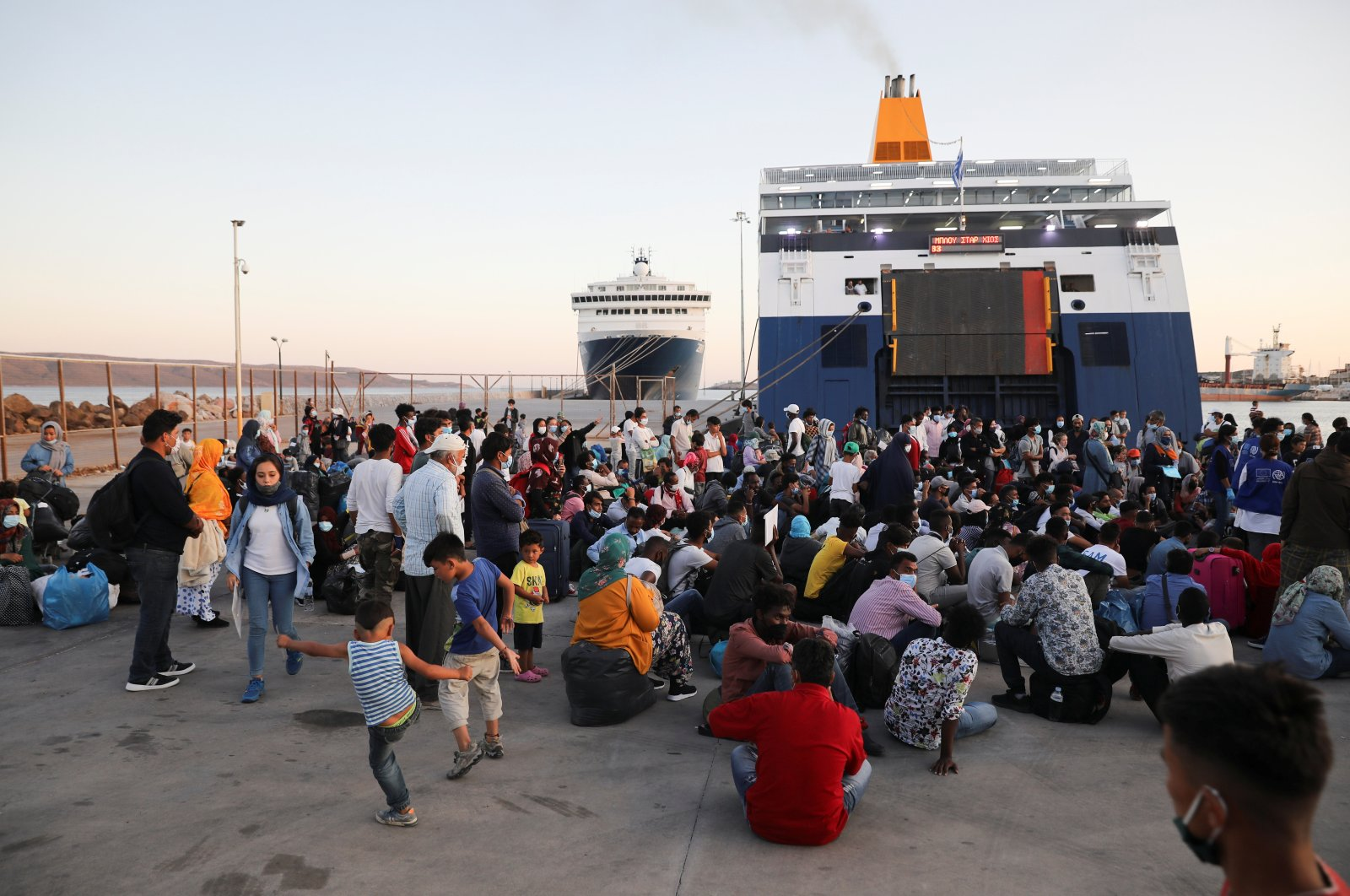 Refugees and migrants wait to be transferred to camps on the mainland after their arrival on a passenger ferry from the island of Lesbos at the port of Lavrio, Greece, Sept. 29, 2020. (Reuters Photo)