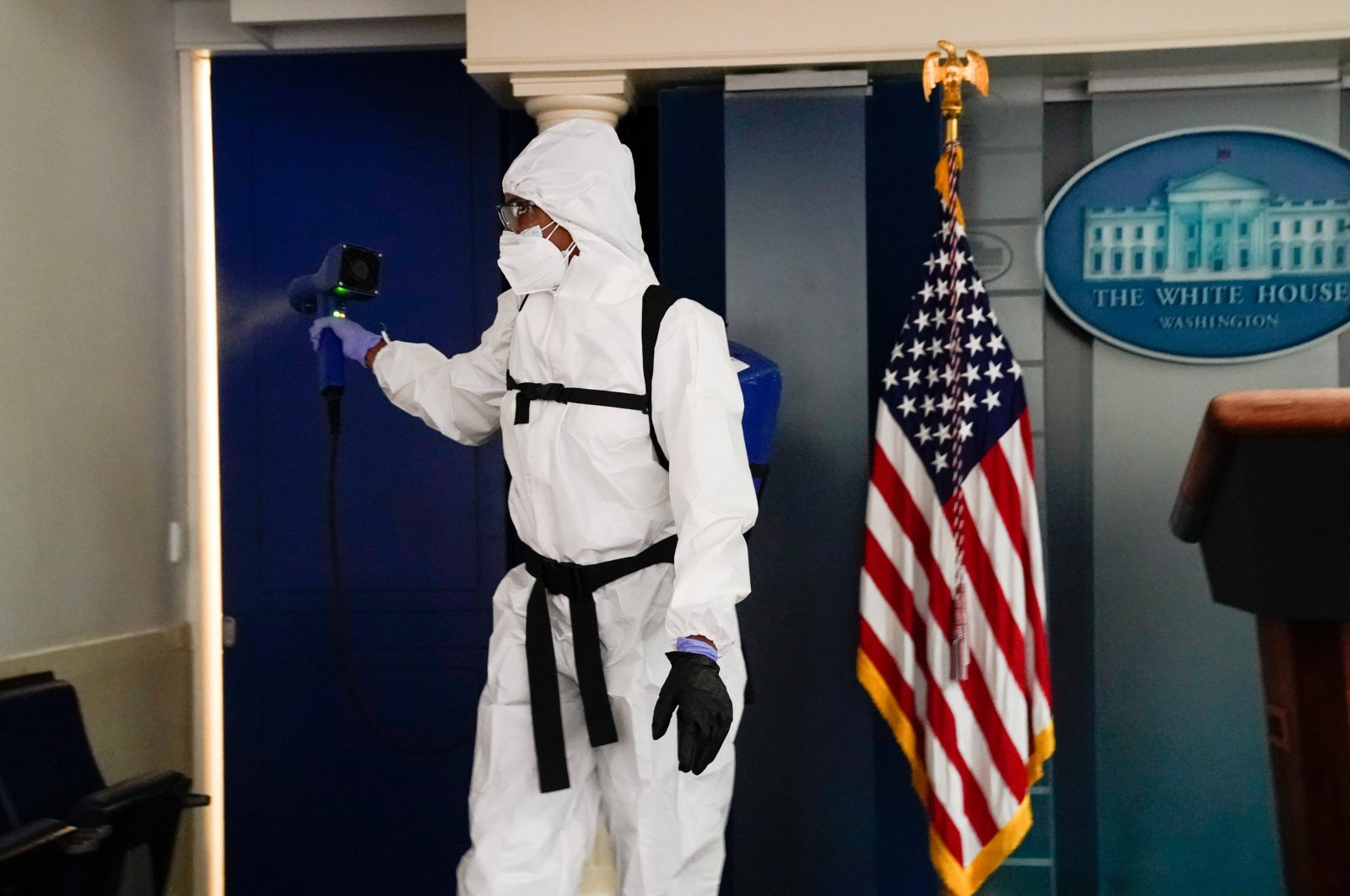 A member of the White House cleaning staff sprays the press briefing room the evening of U.S. President Donald Trump's return from Walter Reed Medical Center after contracting the coronavirus, in Washington, U.S., Oct. 5, 2020. (Reuters Photo)