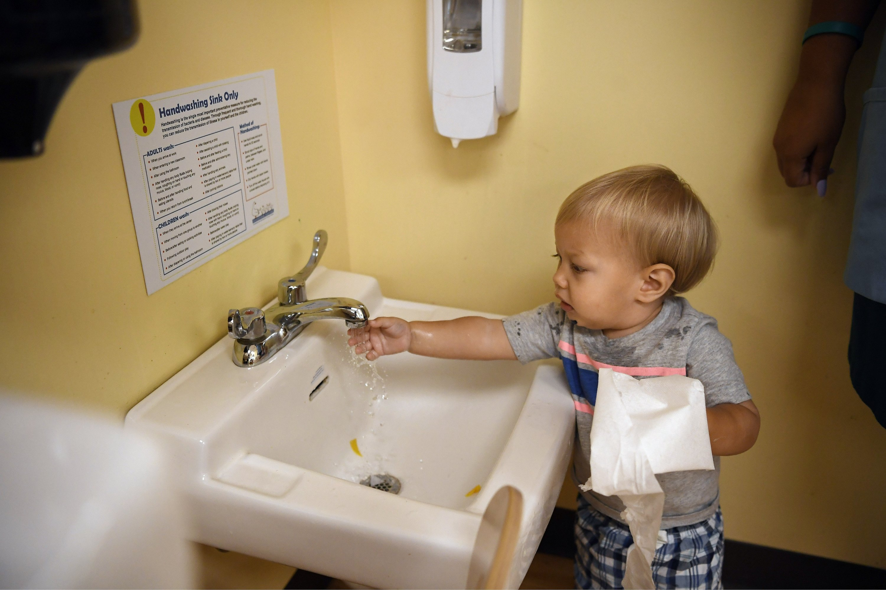 In this Aug. 27, 2020 photo, Owen Skelton washes his hands at Educational Playcare, in Glastonbury, Connecticut. (AP Photo)