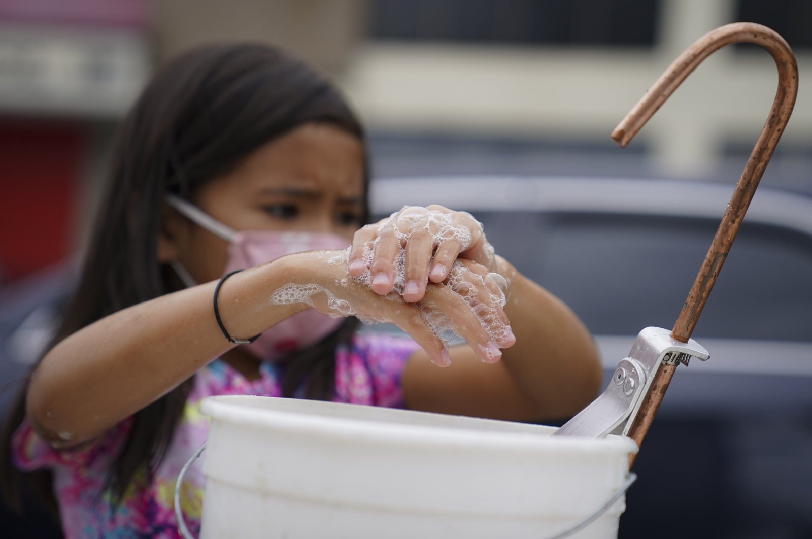 A student washes her hands on a blocked street before participating in an outdoor learning demonstration to display methods schools can use to continue on-site education during the coronavirus pandemic, Sept. 2, 2020, at P.S. 15 in the Brooklyn borough of New York. (AP Photo)