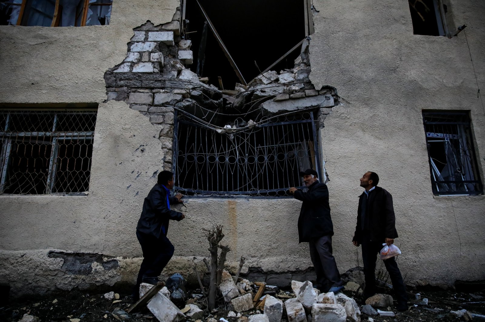 Local residents stand in front of their damaged home hit by artillery fire during the fighting over Nagorno-Karabakh in the city of Terter, Azerbaijan, Oct. 6, 2020. (REUTERS Photo)