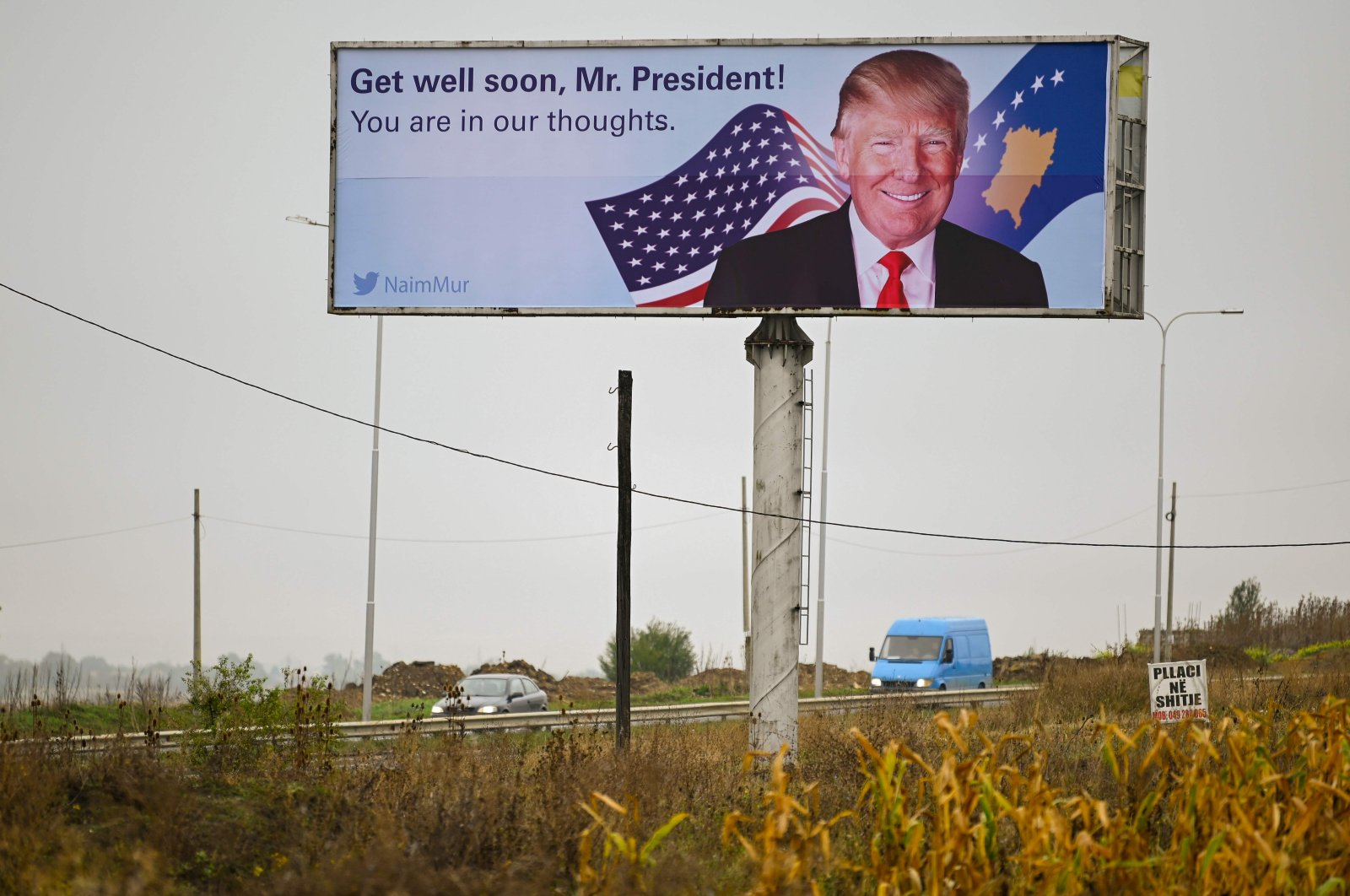 Traffic flows past a billboard wishing U.S. President Donald Trump a speedy recovery from COVID-19, near Pristina International Airport, Kosovo, Oct. 7, 2020. (AFP Photo)