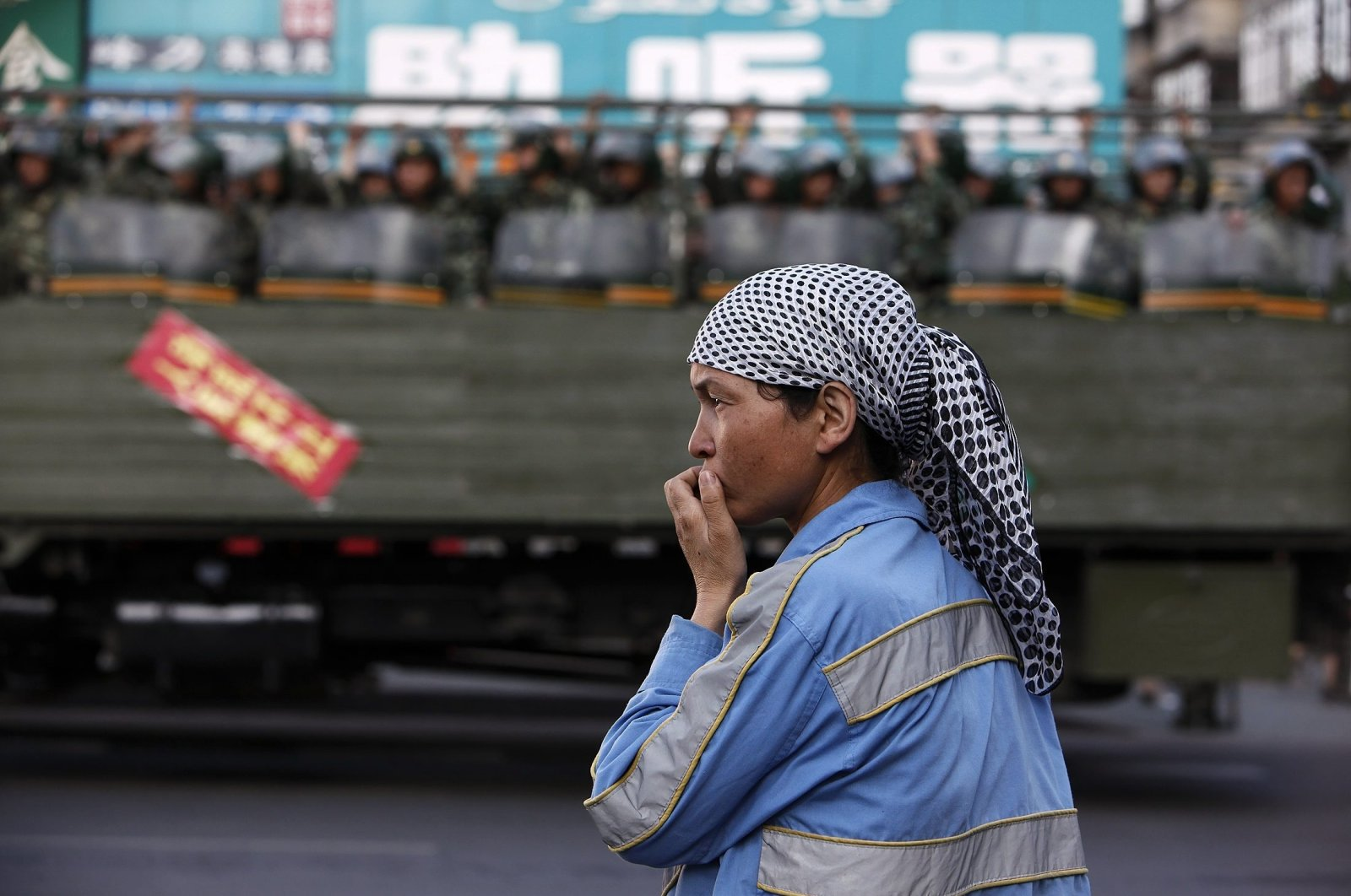 An ethnic Uighur woman stands on the side of a road as Chinese troops stand by on a truck on a main street in Urumqi, China's Xinjiang Autonomous Region, July 9, 2009. (Reuters Photo)