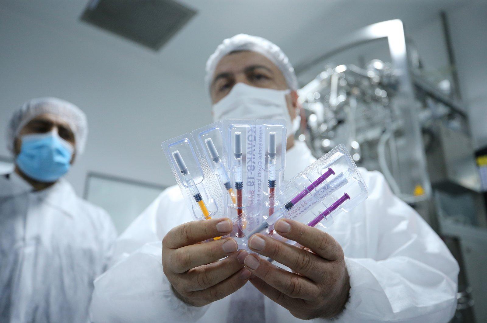 Health Minister Fahrettin Koca shows a vaccine in development by Koçak Farma company, in Tekirdağ, northwestern Turkey, Oct. 3, 2020. (AA Photo)