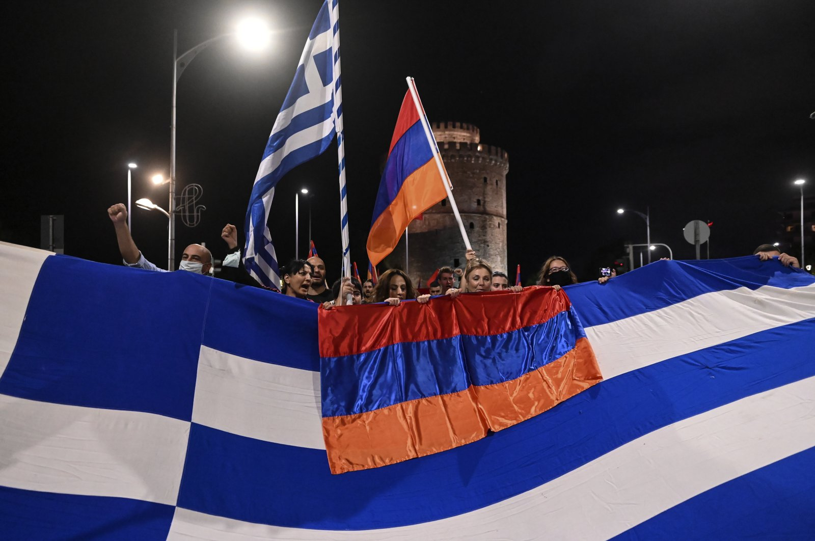 Pro-Armenian protesters stand behind a Greek and an Armenian flag during a demonstration in support of Armenia, in the northern city of Thessaloniki, Greece, Oct. 3, 2020. (AP Photo)