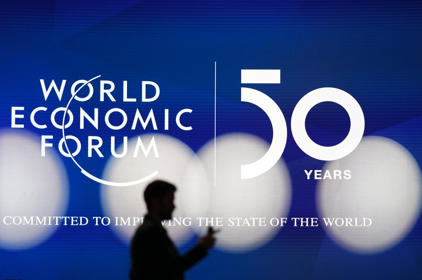 A man's silhouette seen in front of the logo of the World Economic Forum in Davos, Switzerland, Jan. 19, 2020. (AP Photo)
