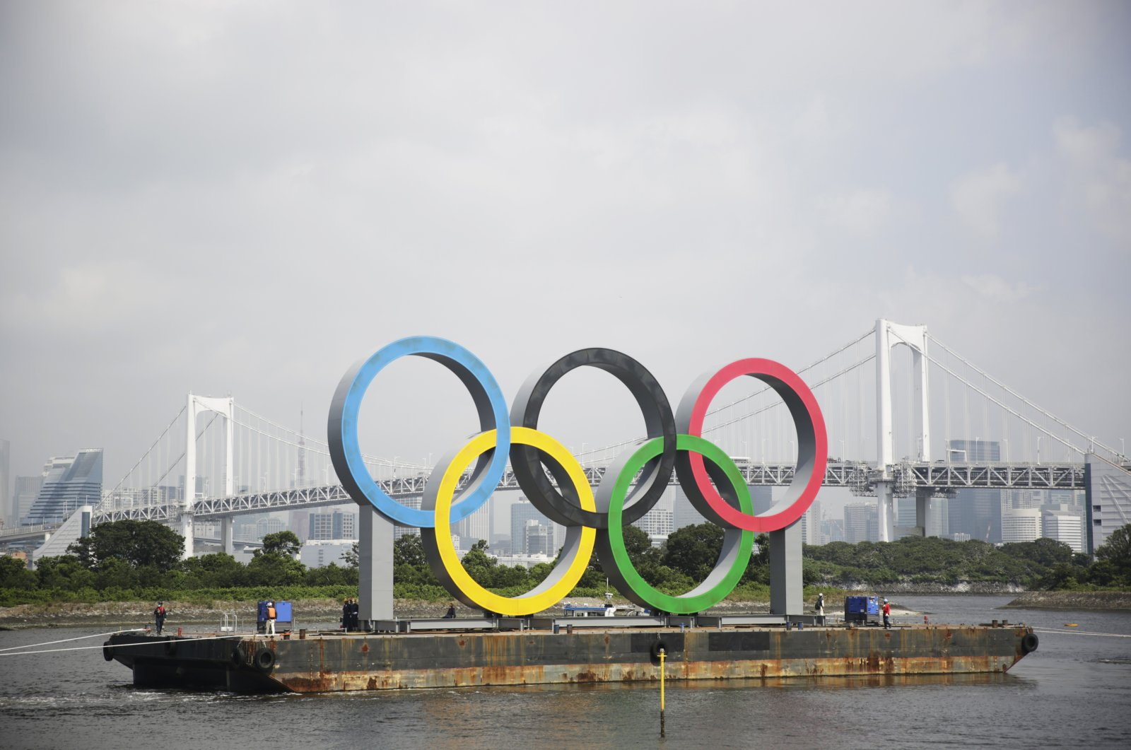 A barge carries the Olympic rings for maintenance due to postponement of the Tokyo 2020 Games, in Tokyo, Japan, Aug. 6, 2020.