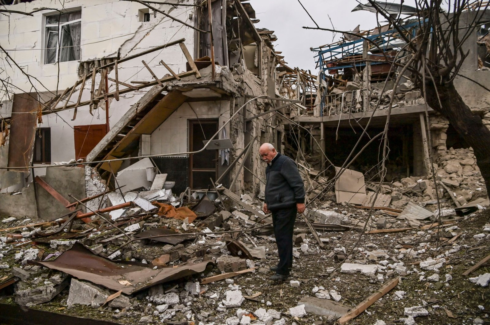 An elderly man stands in front of a destroyed house after shelling in the occupied Nagorno-Karabakh region's main city of Stepanakert., Oct.7, 2020. (AFP)