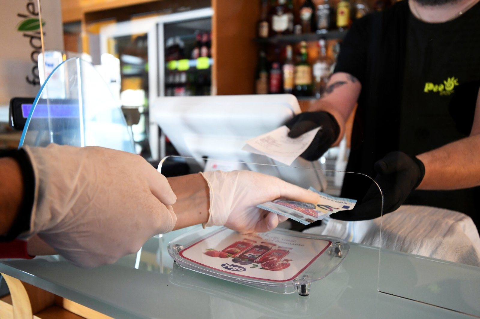A customer wearing gloves pays cash at a restaurant in Castiglione della Pescaia, Italy, April 27, 2020. (Reuters Photo)