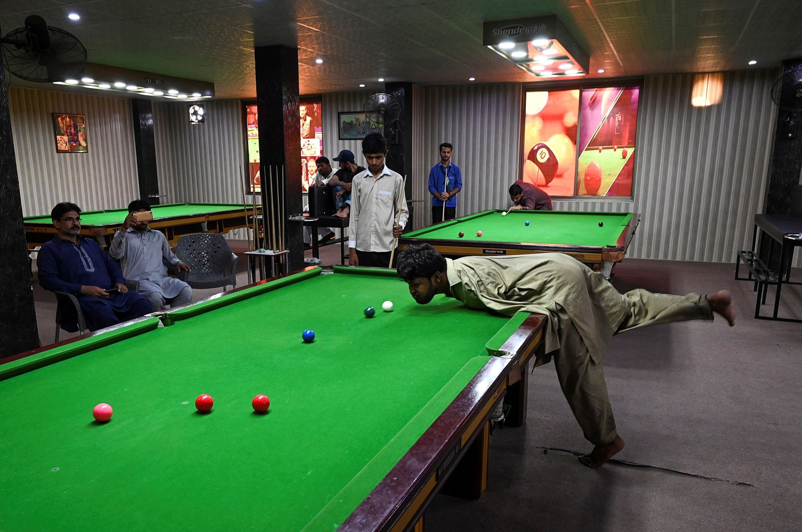 Muhammad Ikram plays a shot with his chin at a local snooker club in Samundri, Pakistan, Sept. 28, 2020. (AFP Photo)