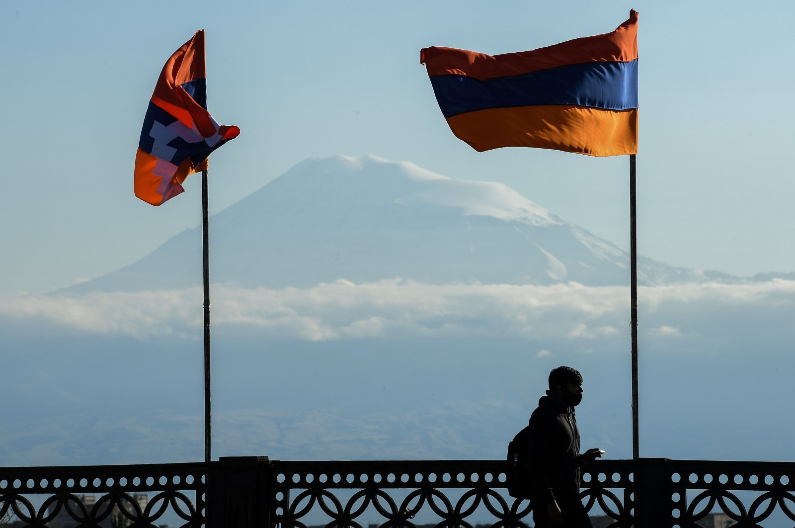 "A man walks over a bridge decorated with the flag of Armenia and the banner of the so-called ""Artsakh Republic"" set up on illegally occupied Azerbaijani territory, with Turkey's Mount Ağrı in the background, in Yerevan on Oct. 7, 2020. (AFP Photo)"