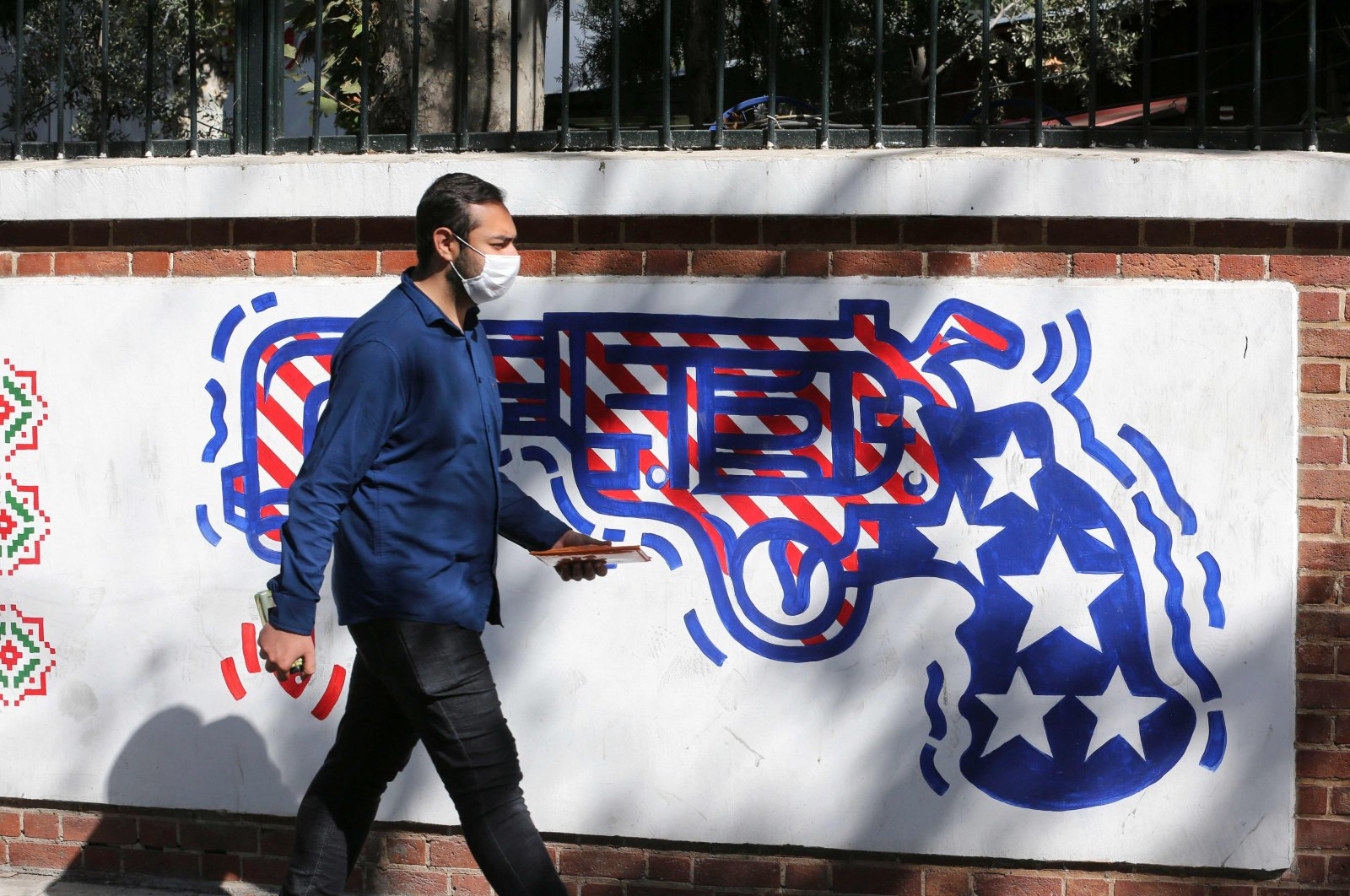 A man walks past a mural painted on the outer walls of the former U.S. embassy in the Iranian capital Tehran, Sept. 29, 2020. (AFP Photo)