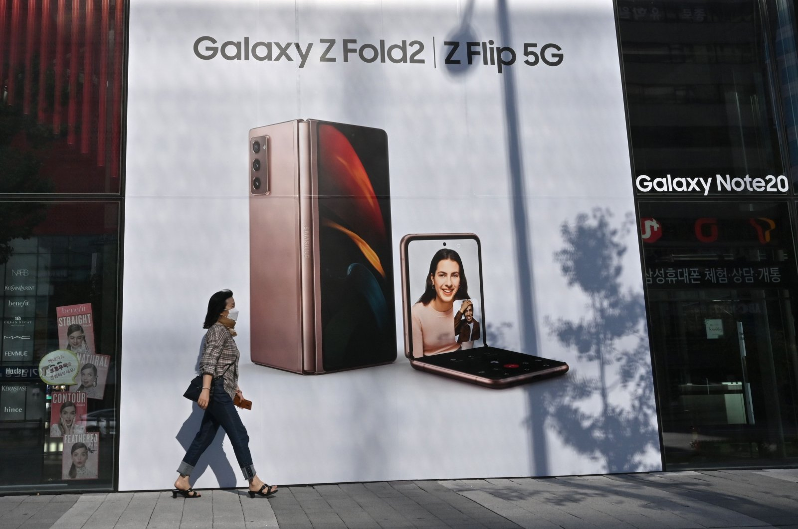 A woman walks past an advertisement for the Samsung Galaxy Z Fold2 and Z Flip smartphones at a Samsung Electronics store in Seoul on Oct. 8, 2020. (AFP Photo)