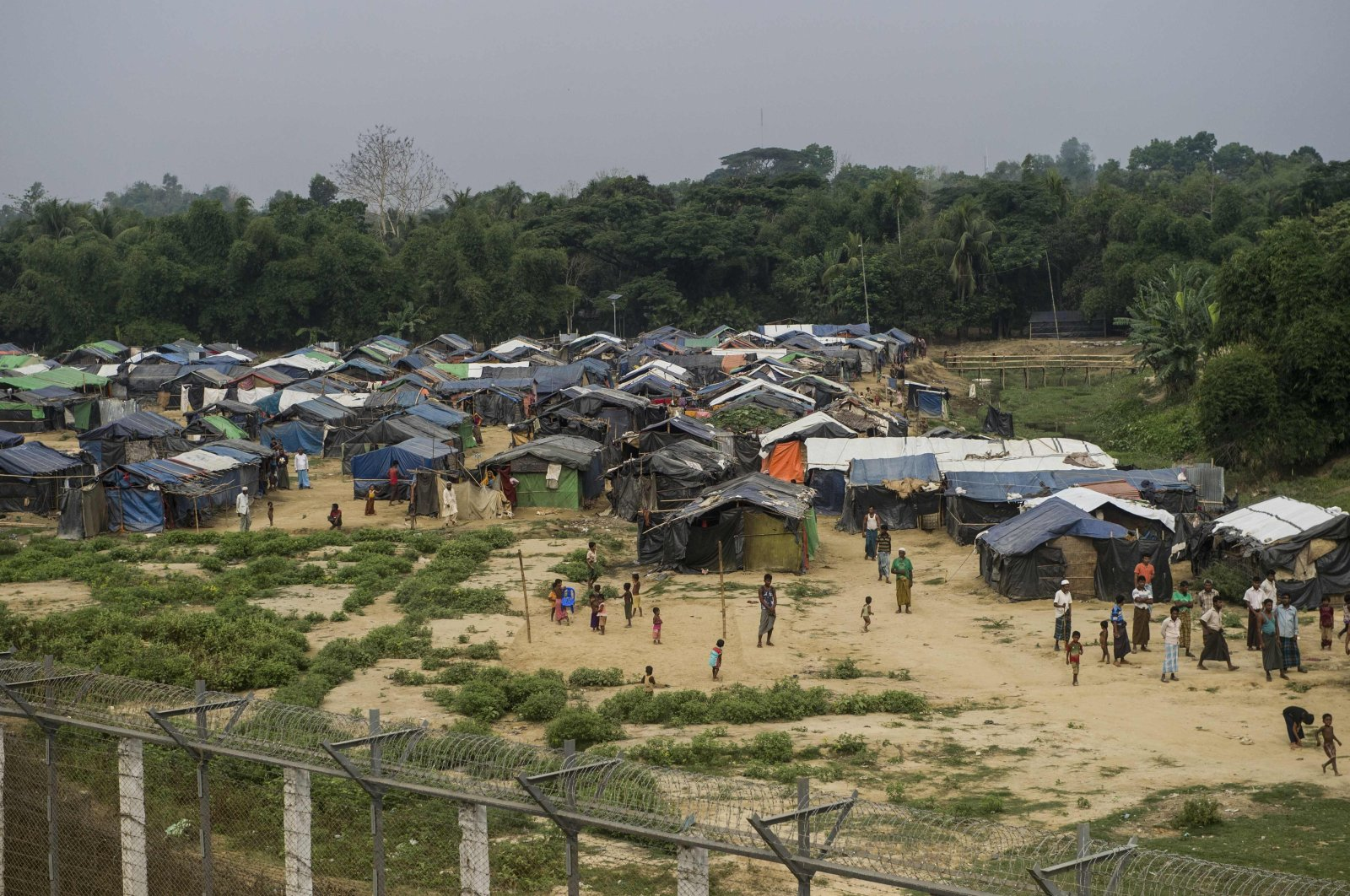 Rohingya refugees gather near their shelters behind Myanmar's border lined with barbed wire fences in Maungdaw district, Rakhine state, April 25, 2018. (AFP Photo)