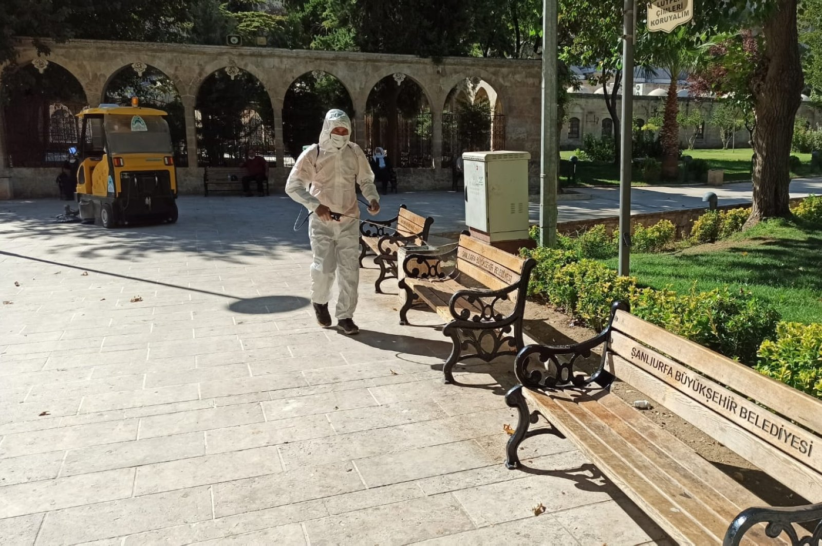 A worker disinfects benches as a precaution against COVID-19 at Balıklıgöl, a popular tourist attraction in Şanlıurfa, southeastern Turkey, Oct. 8, 2020. (AA Photo)