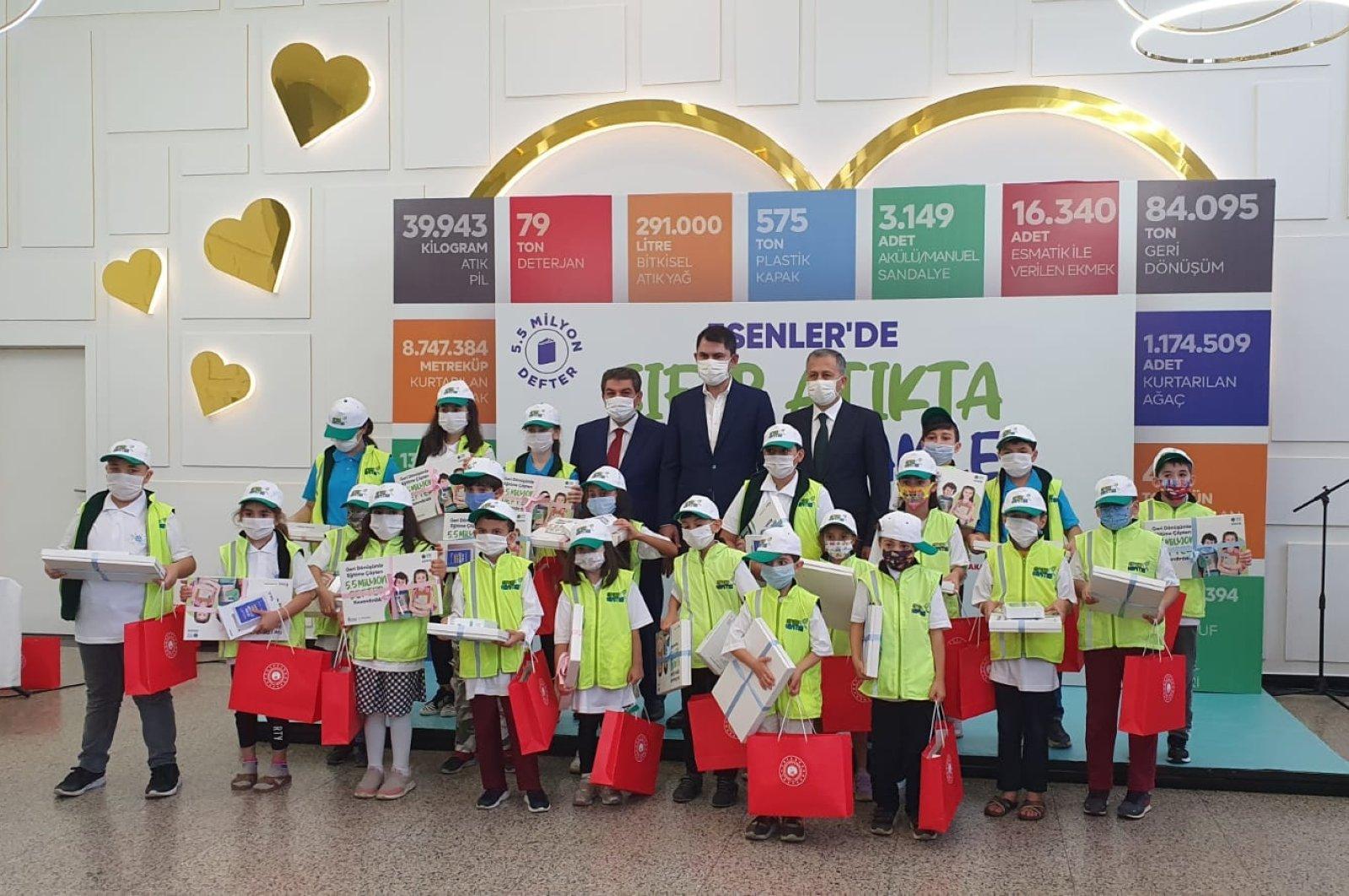 Environment and Urbanization Minister Murat Kurum, Esenler Mayor Tevfik Göksu and Istanbul Governor Ali Yerlikaya pose with children who received recycled notebooks, Istanbul, Turkey, Oct. 8, 2020. (DHA Photo)