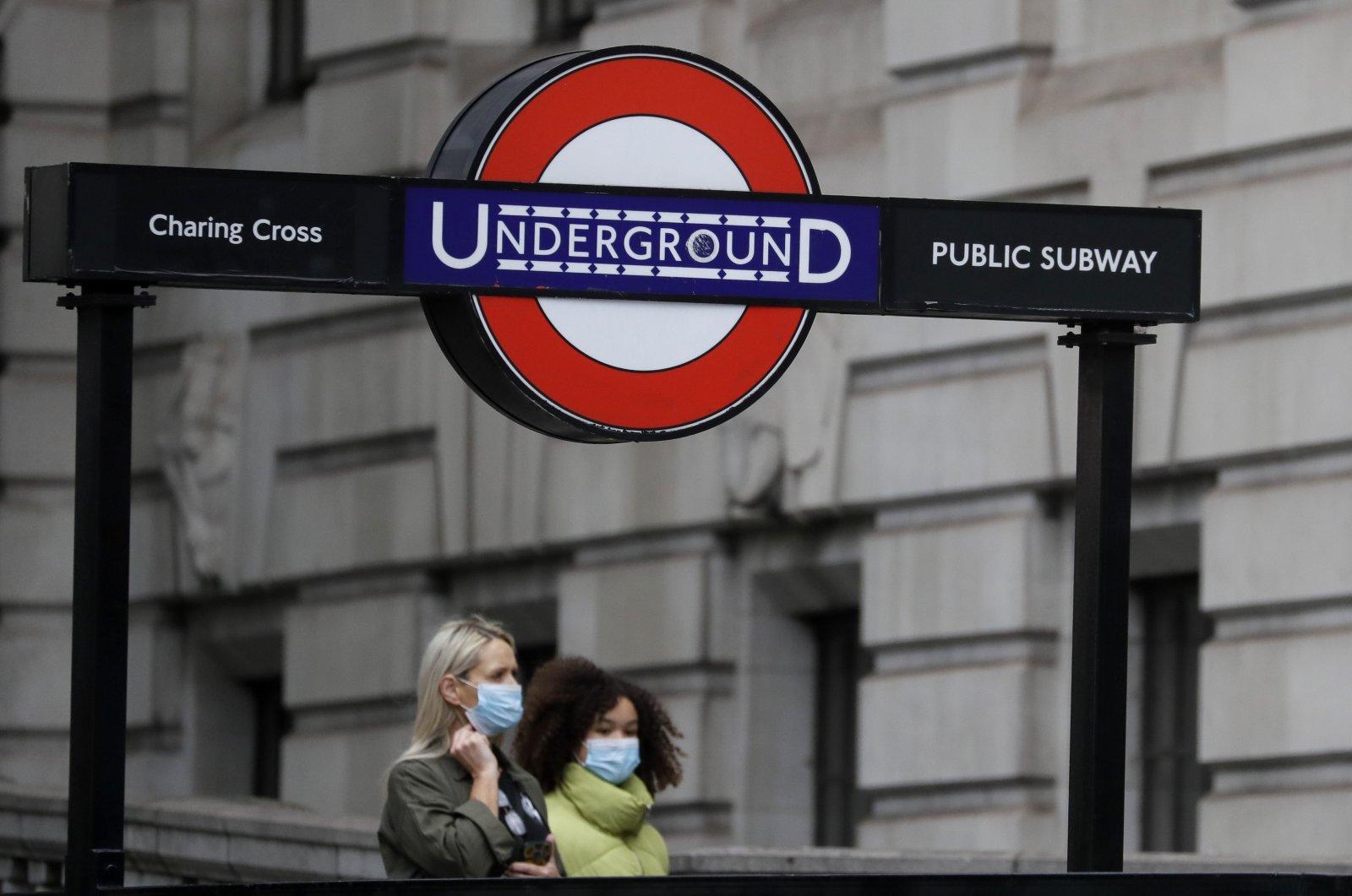 Pedestrians wear masks as they walk near a subway station in London, U.K., June 5, 2020. (AP Photo)