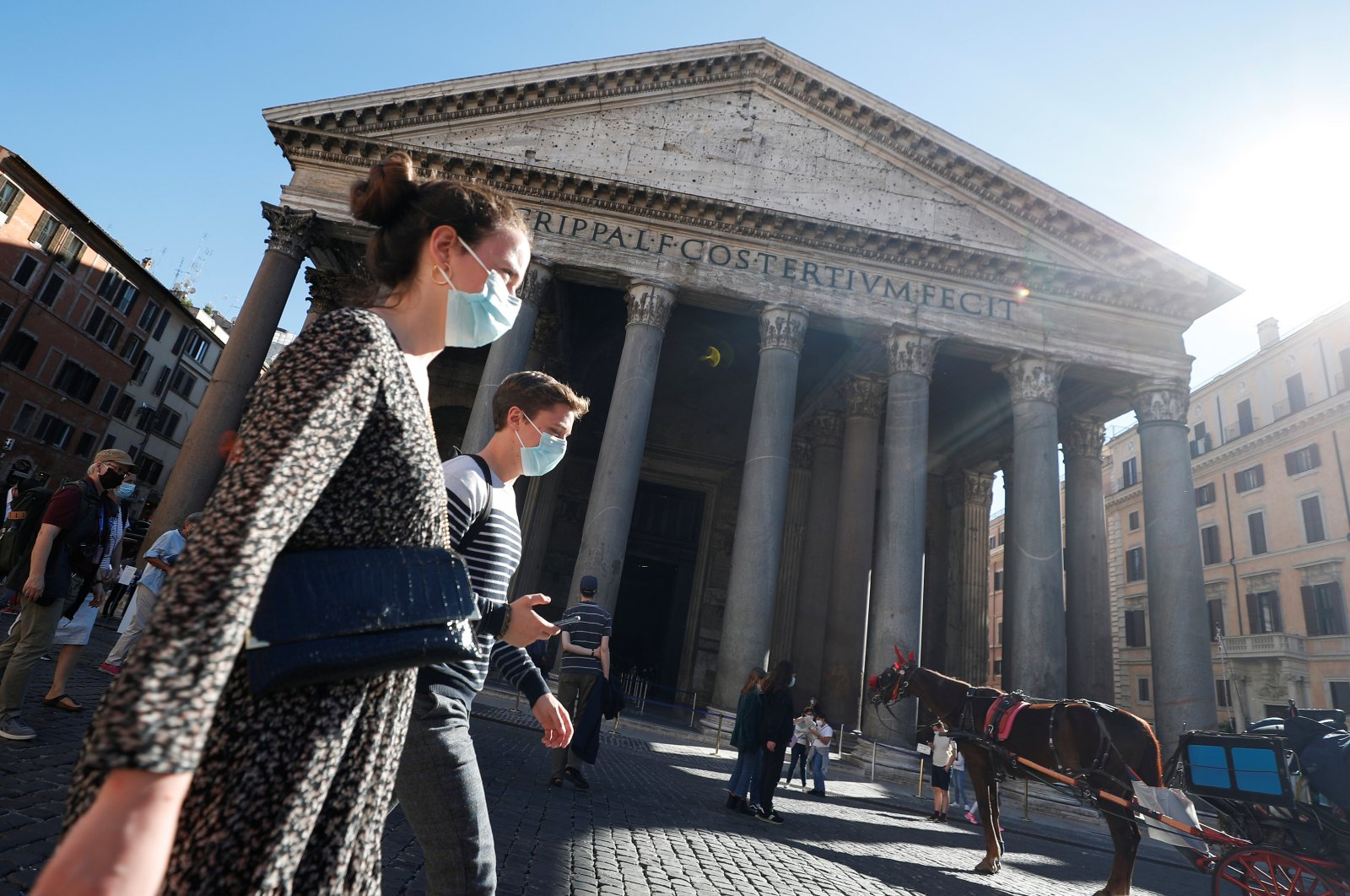 People wearing protective masks walk past the Pantheon as local authorities in the Italian capital Rome ordered face coverings to be worn at all times outdoors, in an effort to counter the spread of COVID-19, in Rome, Italy, Oct. 8, 2020. (Reuters Photo)