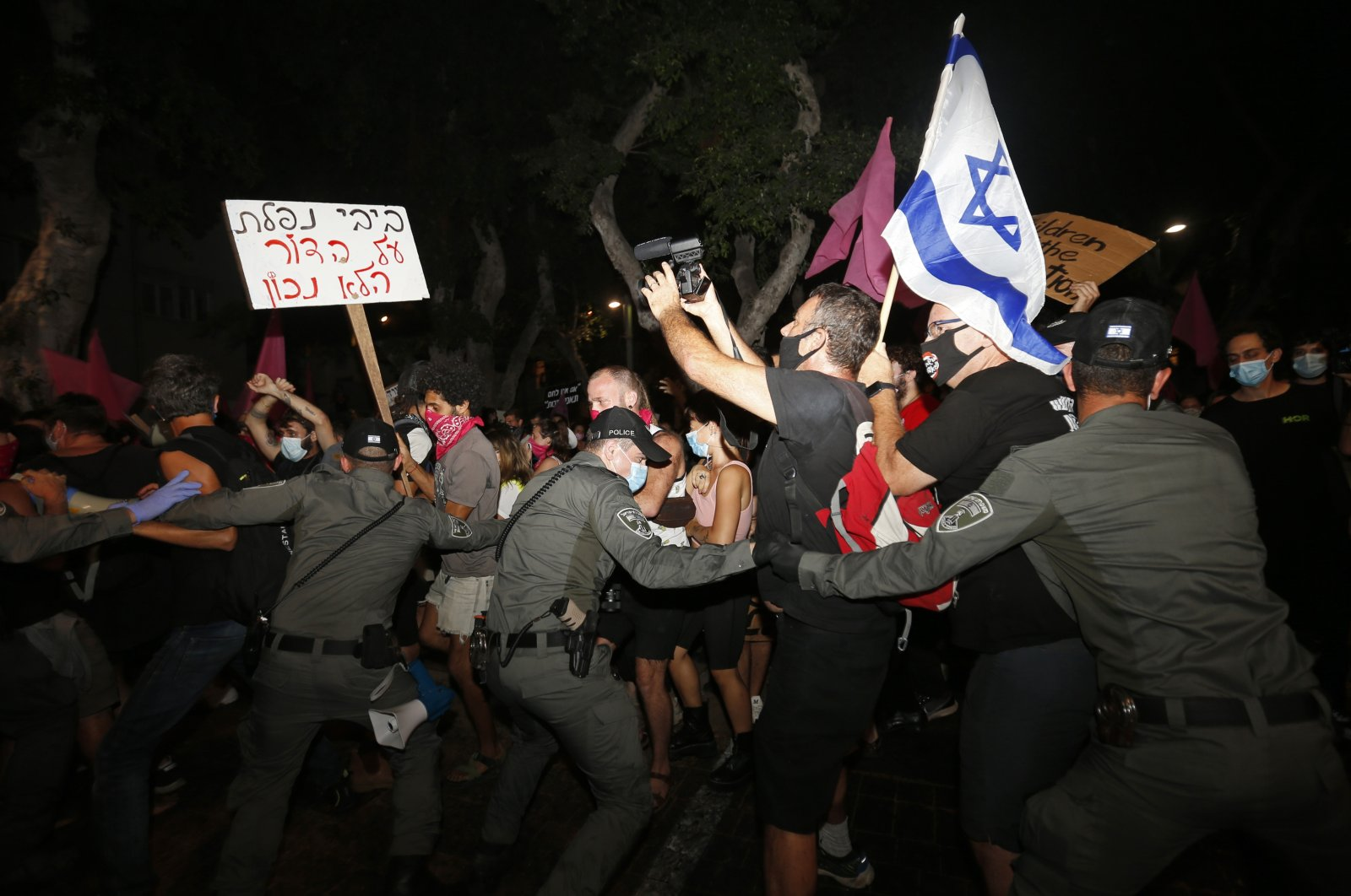 Israeli police scuffle with protesters during a demonstration against Prime Minister Benjamin Netanyahu in Tel Aviv, Israel, Oct. 6, 2020. (AP Photo)