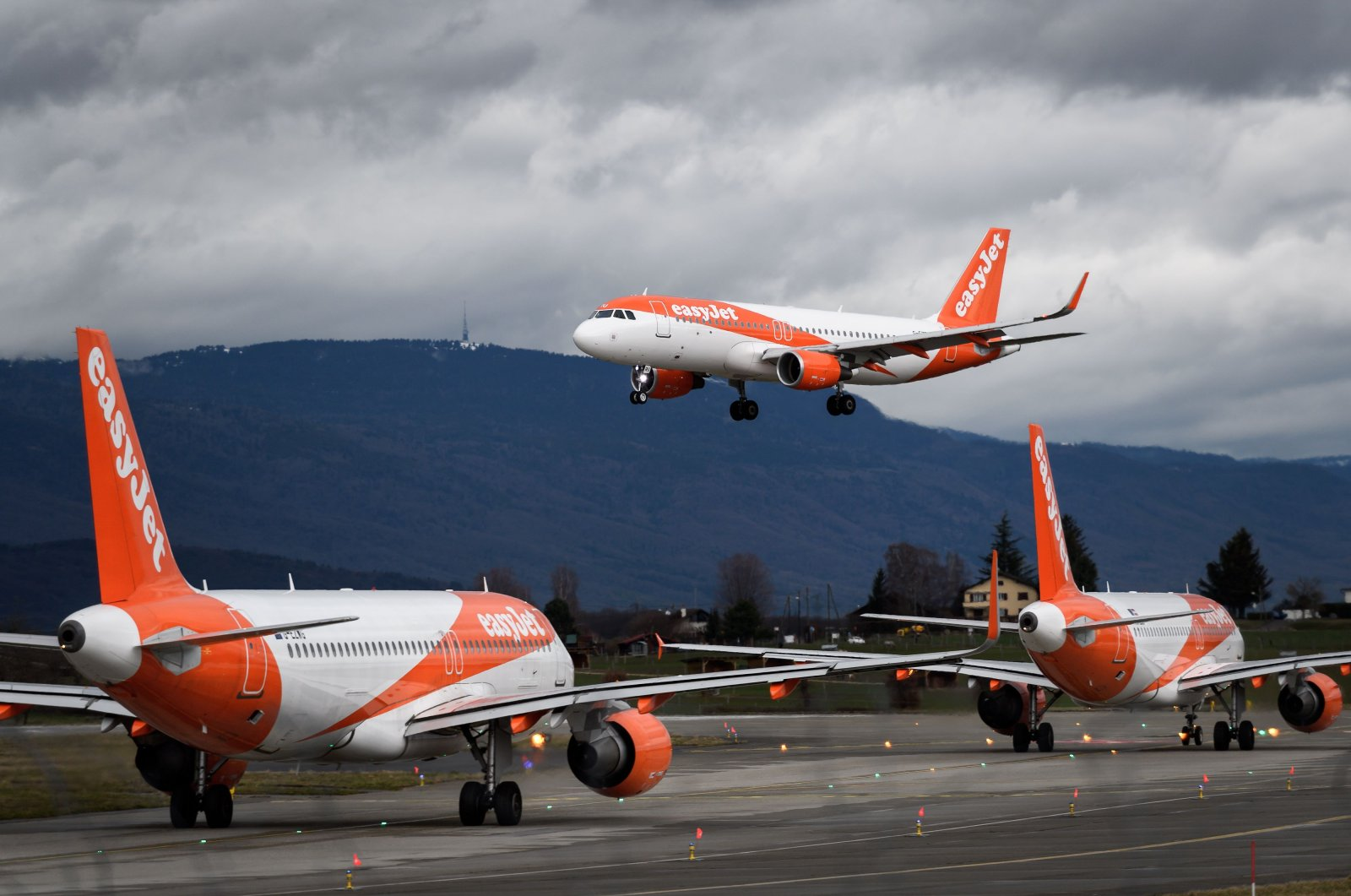An Airbus A320 commercial plane of low-cost carrier EasyJet is seen landing above two other planes at Geneva Airport, in Geneva on March 10, 2019. (AFP Photo)