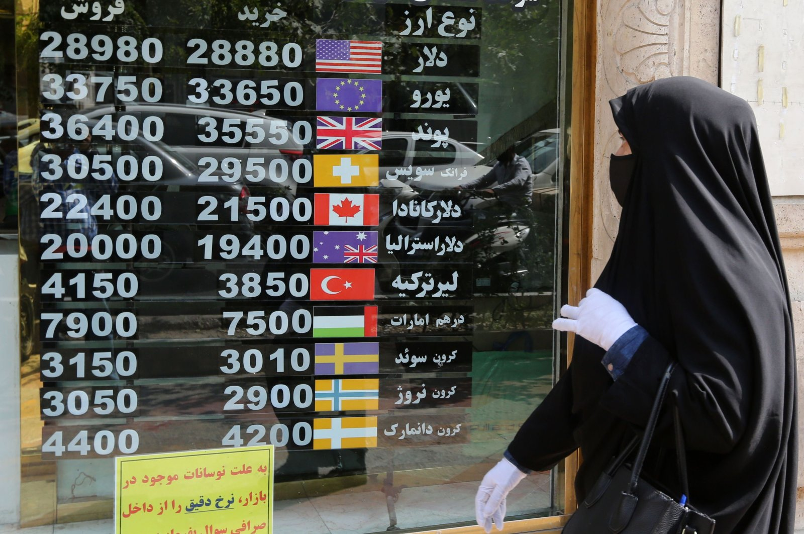 A woman checks a display board at a currency exchange shop as she walks by in the capital Tehran, Iran, Sept. 29, 2020. (AFP Photo)