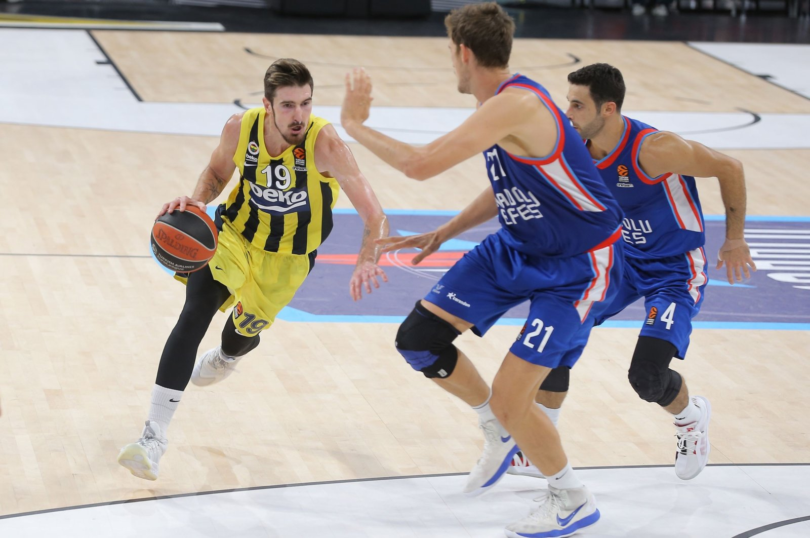 Fenerbahçe's Nando de Colo (L) tries to dribble past Anadolu Efes' Tibor Pleiss (C) and Doğuş Balbay during a EuroLeague basketball match, in Istanbul, Turkey, Oct. 8, 2020. (IHA Photo)