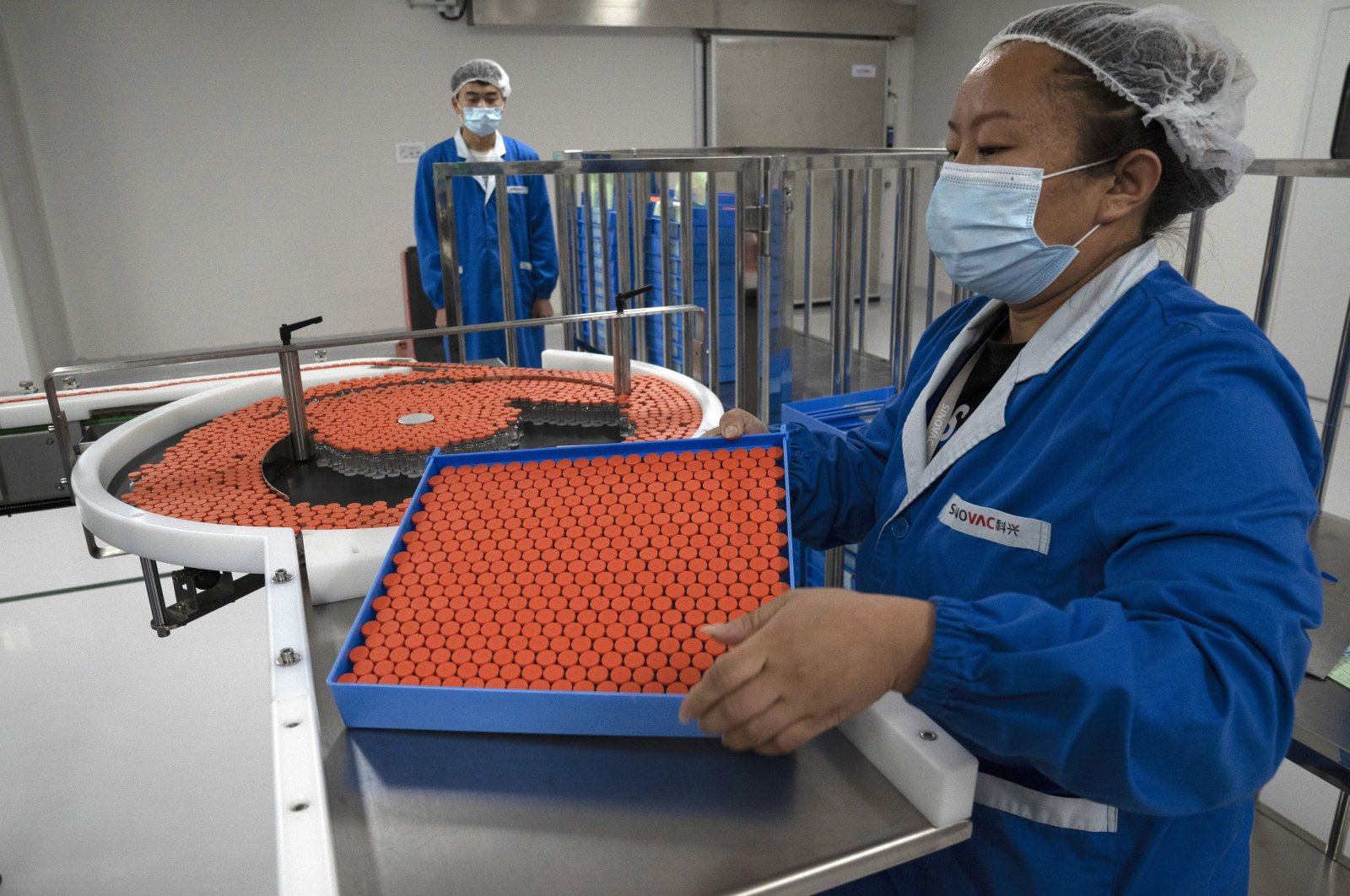 A worker feeds vials for production of SARS CoV-2 Vaccine for COVID-19 at the SinoVac vaccine factory in Beijing, Sept. 24, 2020. (AP Photo)