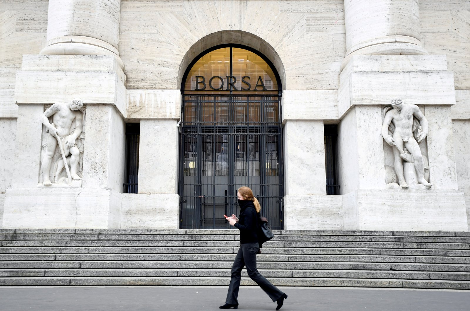 A woman passes the Italian Stock Exchange in Milan, Italy, Feb. 25, 2020. (Reuters Photo)