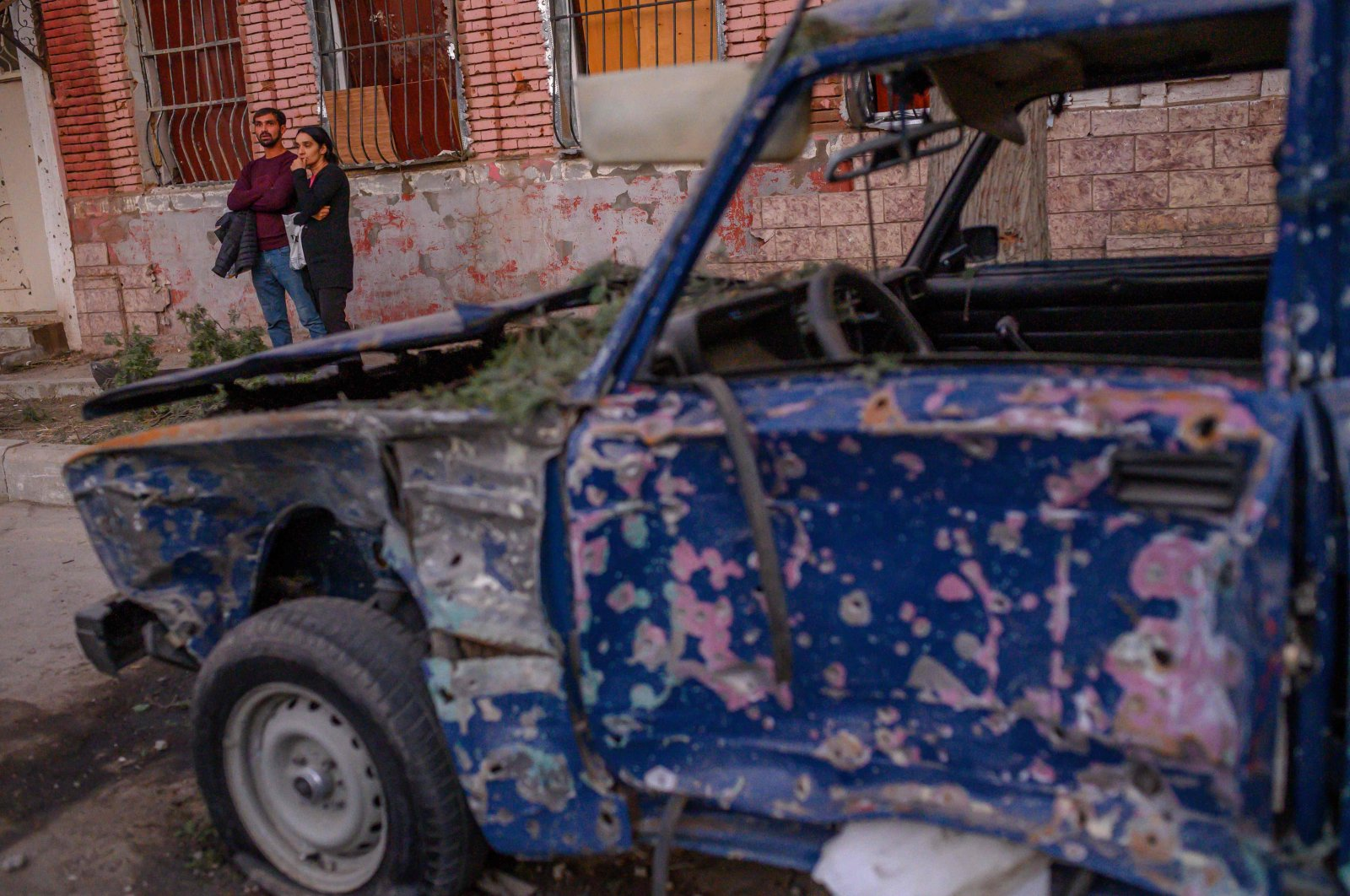 Local residents stand in a street near a damaged car after it was hit by a missile in Gandja, Azerbaijan, Oct. 8, 2020. (AFP Photo)
