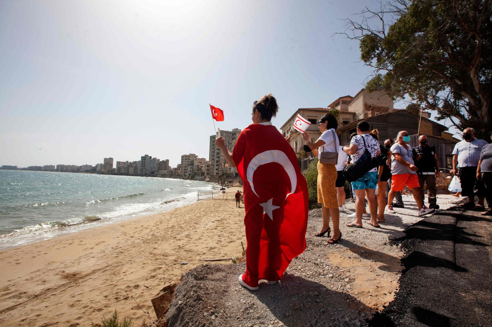 A woman holds the flags of Turkey and the Turkish Republic of Northern Cyprus (TRNC) as she enters Varosha, in the fenced-off area of Famagusta, Cyprus, Oct. 8, 2020. (AFP Photo)
