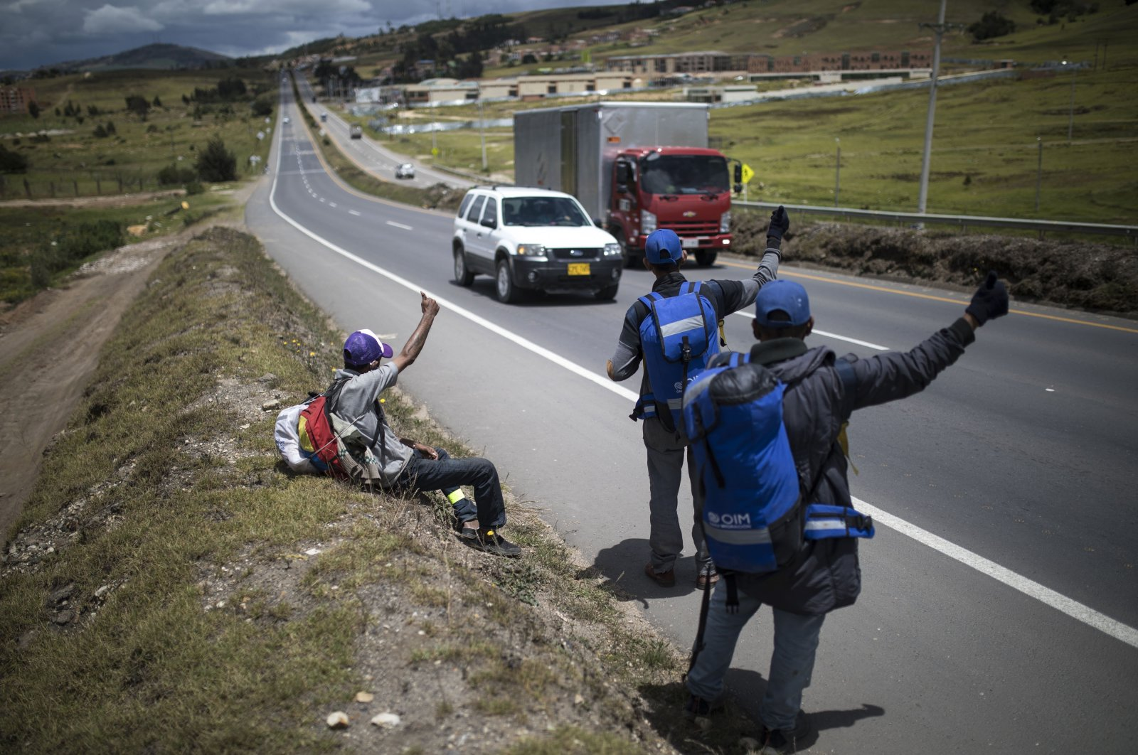 Venezuelan migrants hitchhike toward the capital, in Tunja, Colombia, Oct. 6, 2020. (AP Photo)