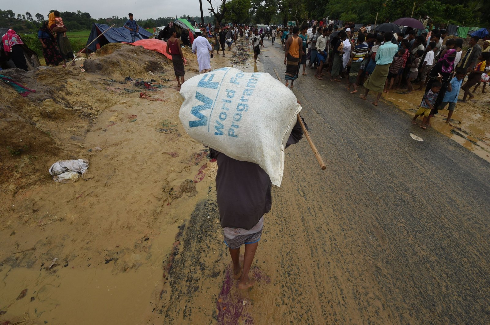 Rohingya Muslim refugee carries a rice bag distributed by the World Food Programme along a road close to Balukhali refugee camp near Gumdhum, Bangladesh, Sept. 17, 2017. (AFP Photo)