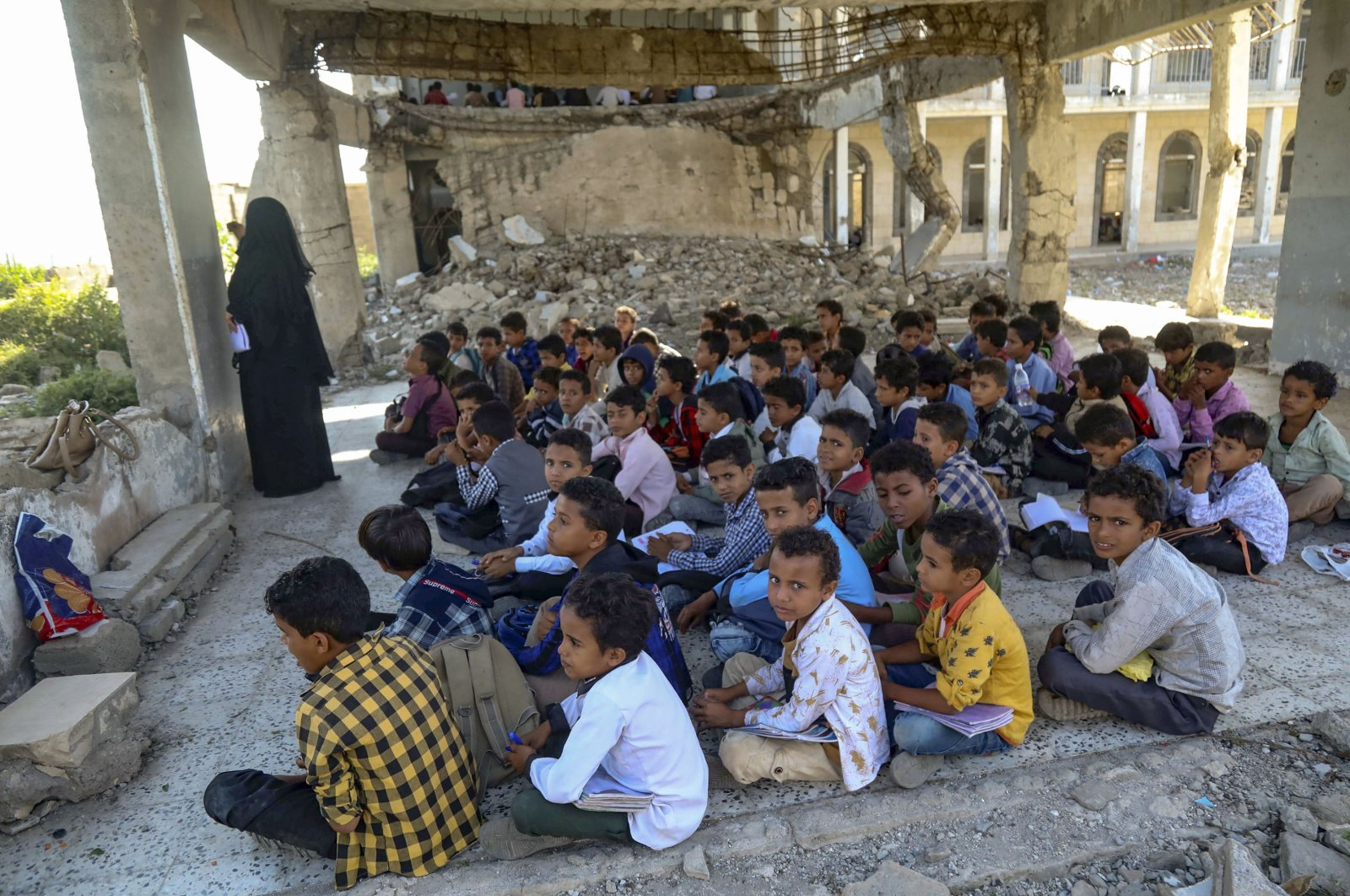 Yemeni pupils attend class on the first day of the new academic year in a makeshift classroom in their school compound, which was heavily damaged two years ago in an air strike, in the country's third-city of Taez on Oct. 7, 2020. (AFP Photo)